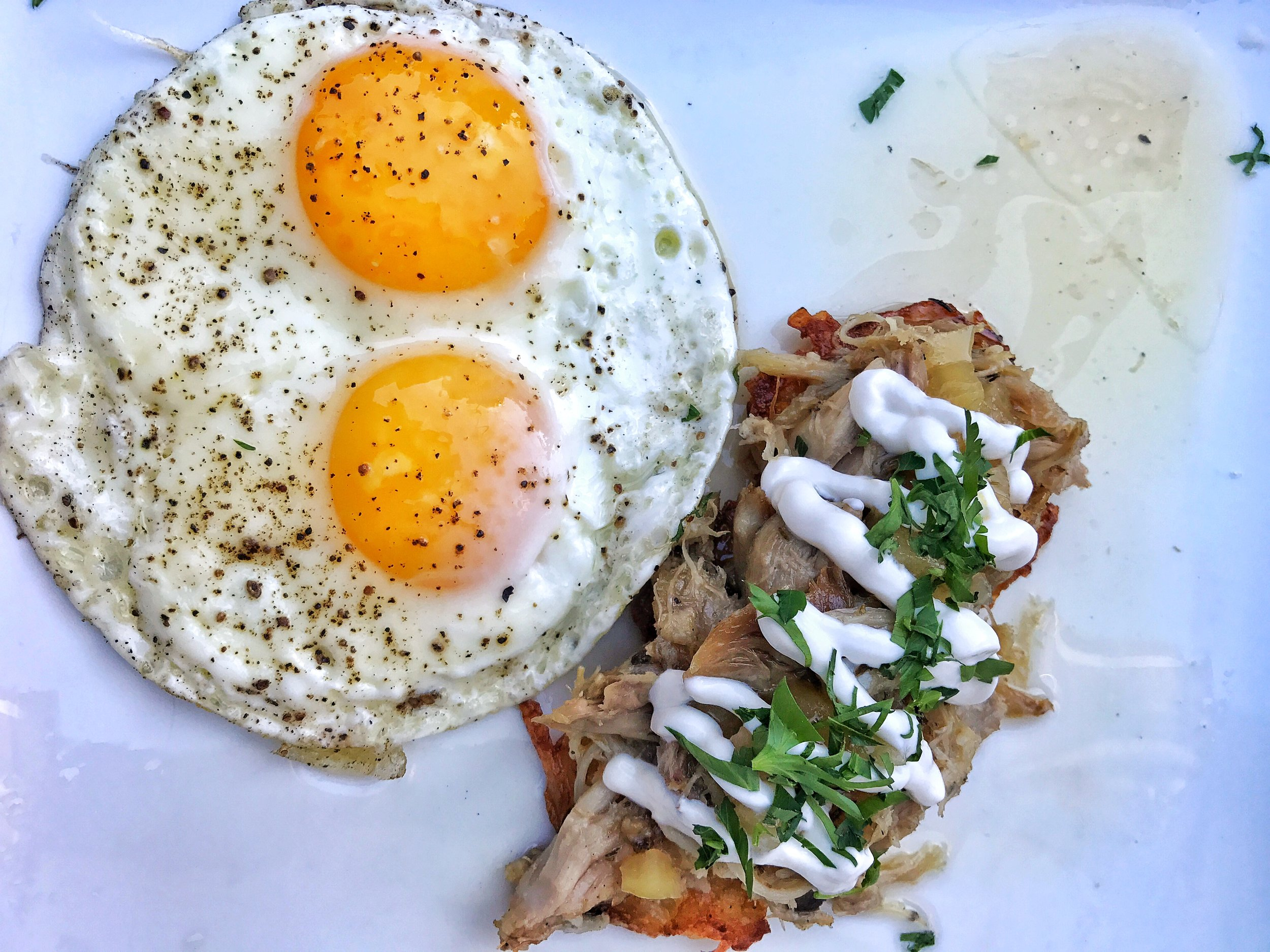 Chicken confit and potato latkes with sunnyside up eggs and apple thyme jam with sour cream on top