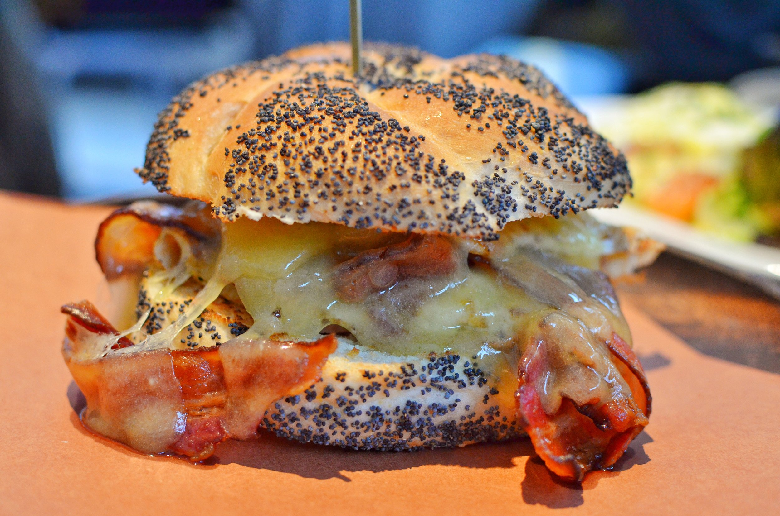 Egg sandwich with bacon, two fried eggs, melted cheddar cheese, pesto on a poppy seed Kaiser roll