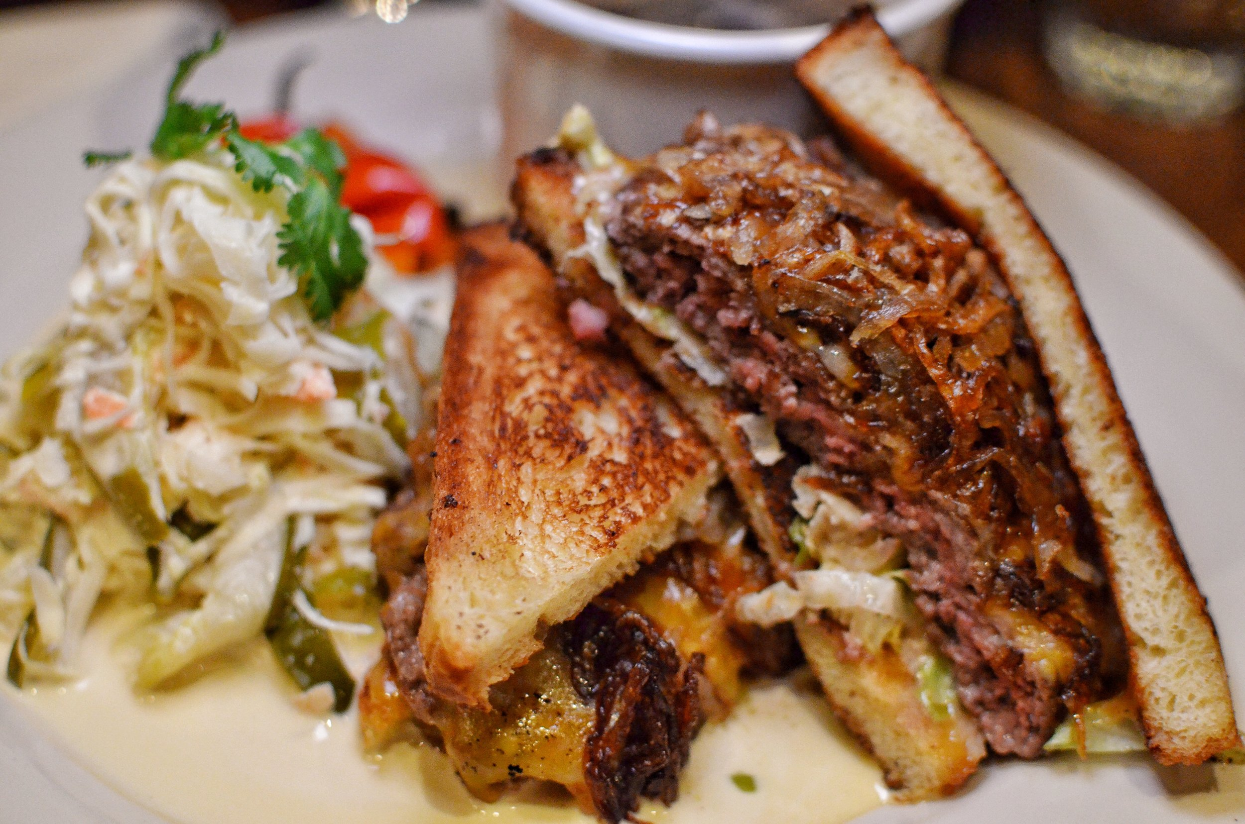 Patty melt on buttermilk bread, American cheese, Maison special sauce served with coleslaw and au jus