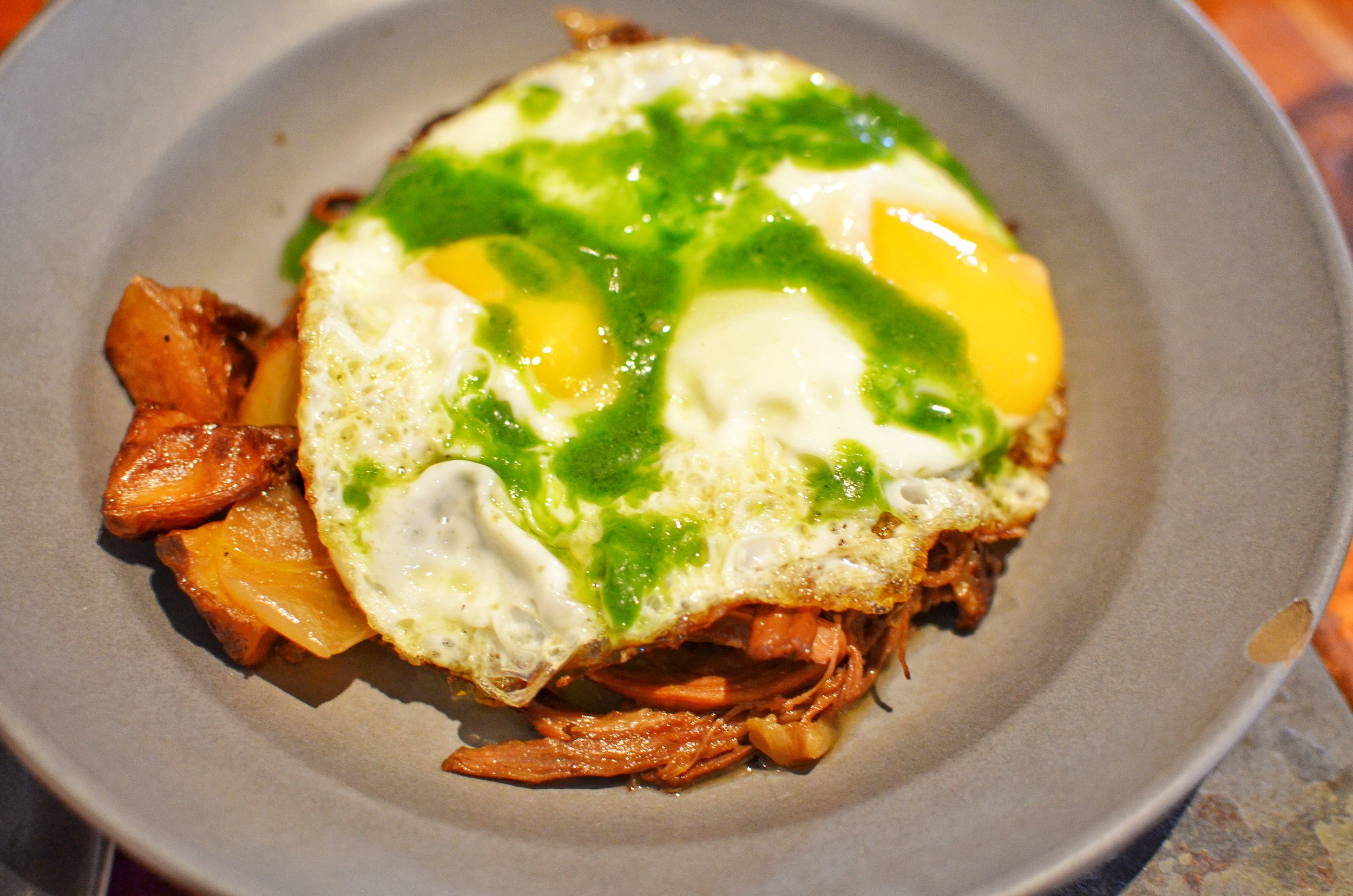 Grass fed beef hash with yukon potatoes, two fried eggs, salsa verde and cramalized onions