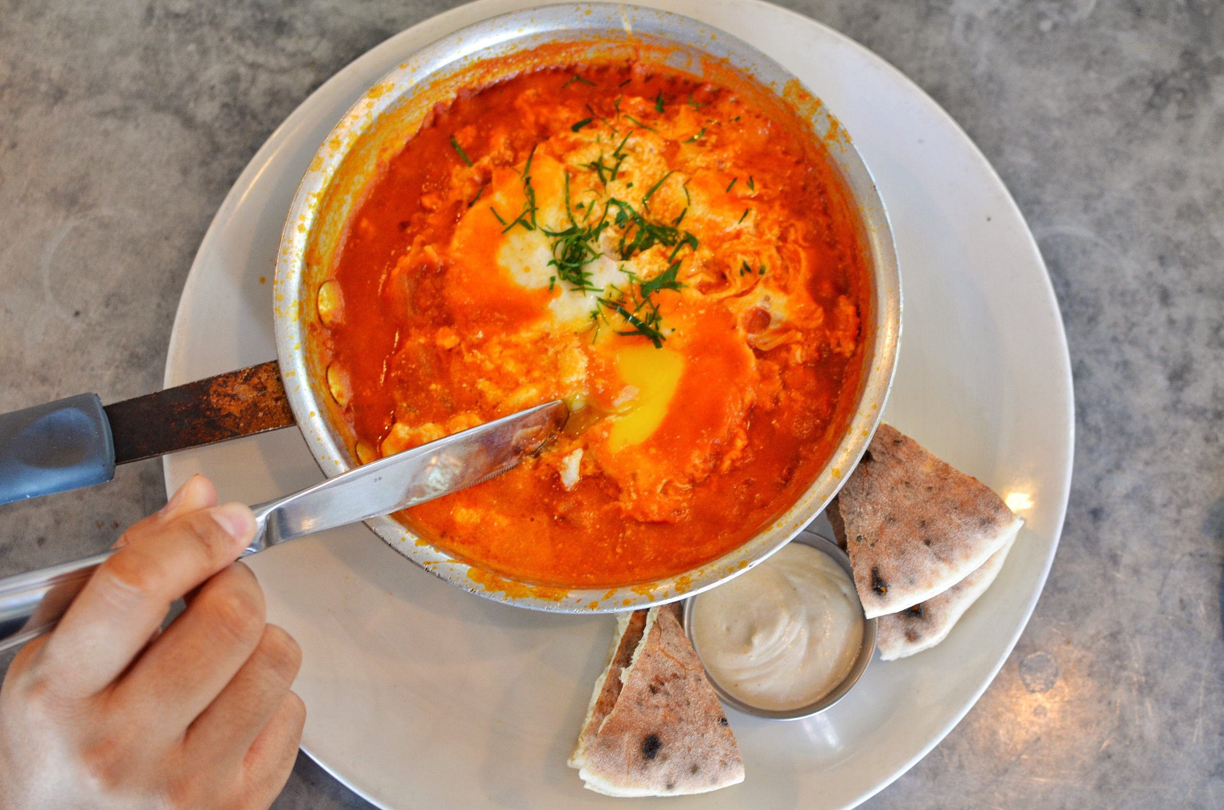 Shakshuka- Baked eggs and a spicy tomato onion sauce, tahini