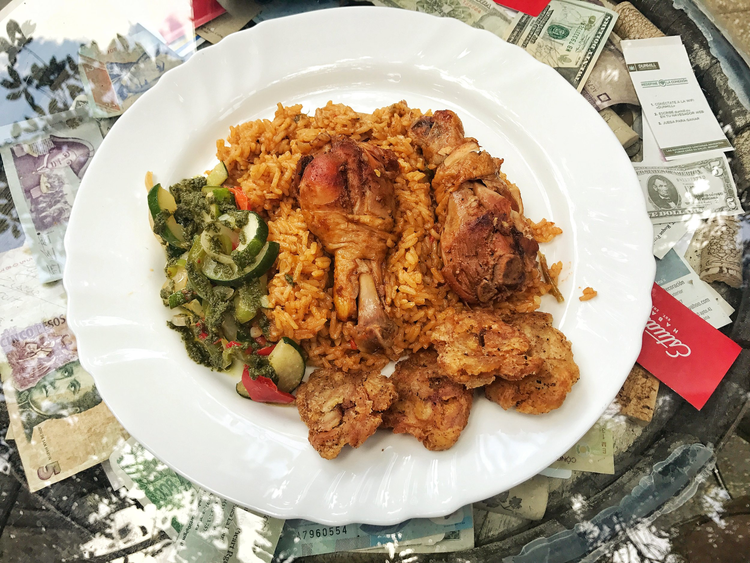 Roasted chicken legs with tostones, paella like rice, vegetables with a chimmichuri sauce