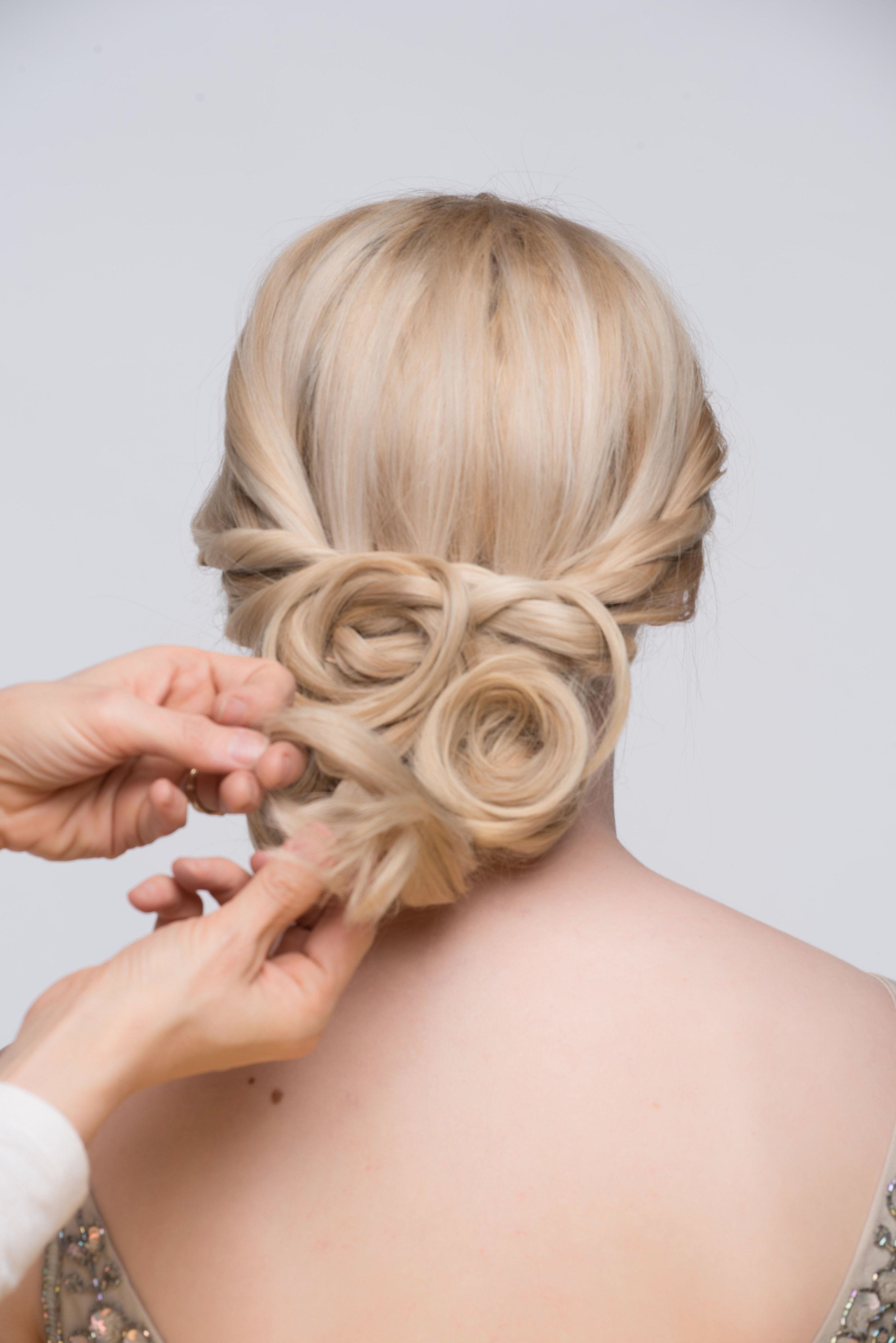 Continue to pin the bottom pieces into the style. Directing the hair to the middle of the head and changing up the pattern to get a unique glam look. Spray any loose hairs into place with a finishing spray.