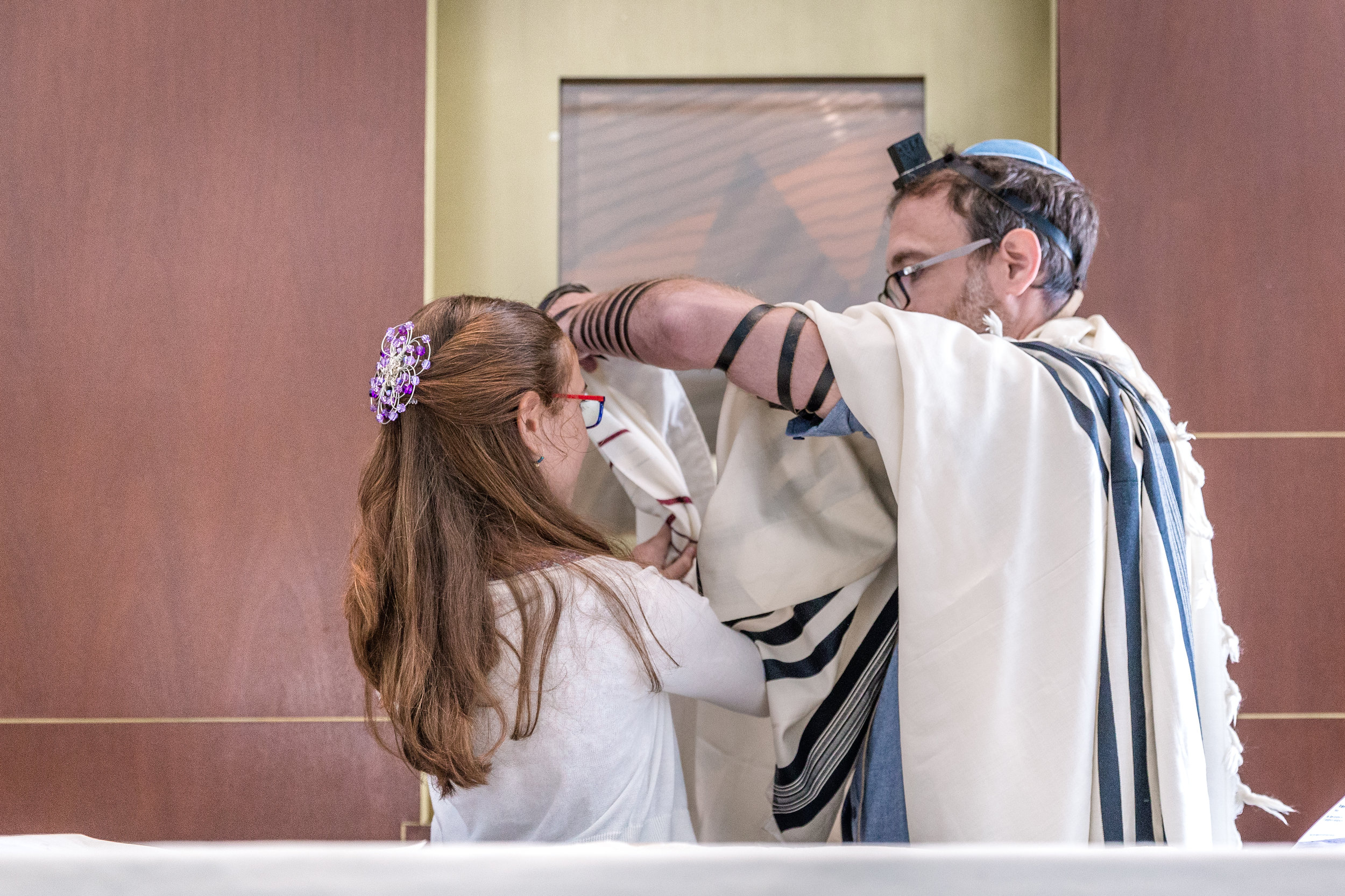 Meirav is wrapped in a tallit - the traditional Jewish prayer shawl - by her Father. -