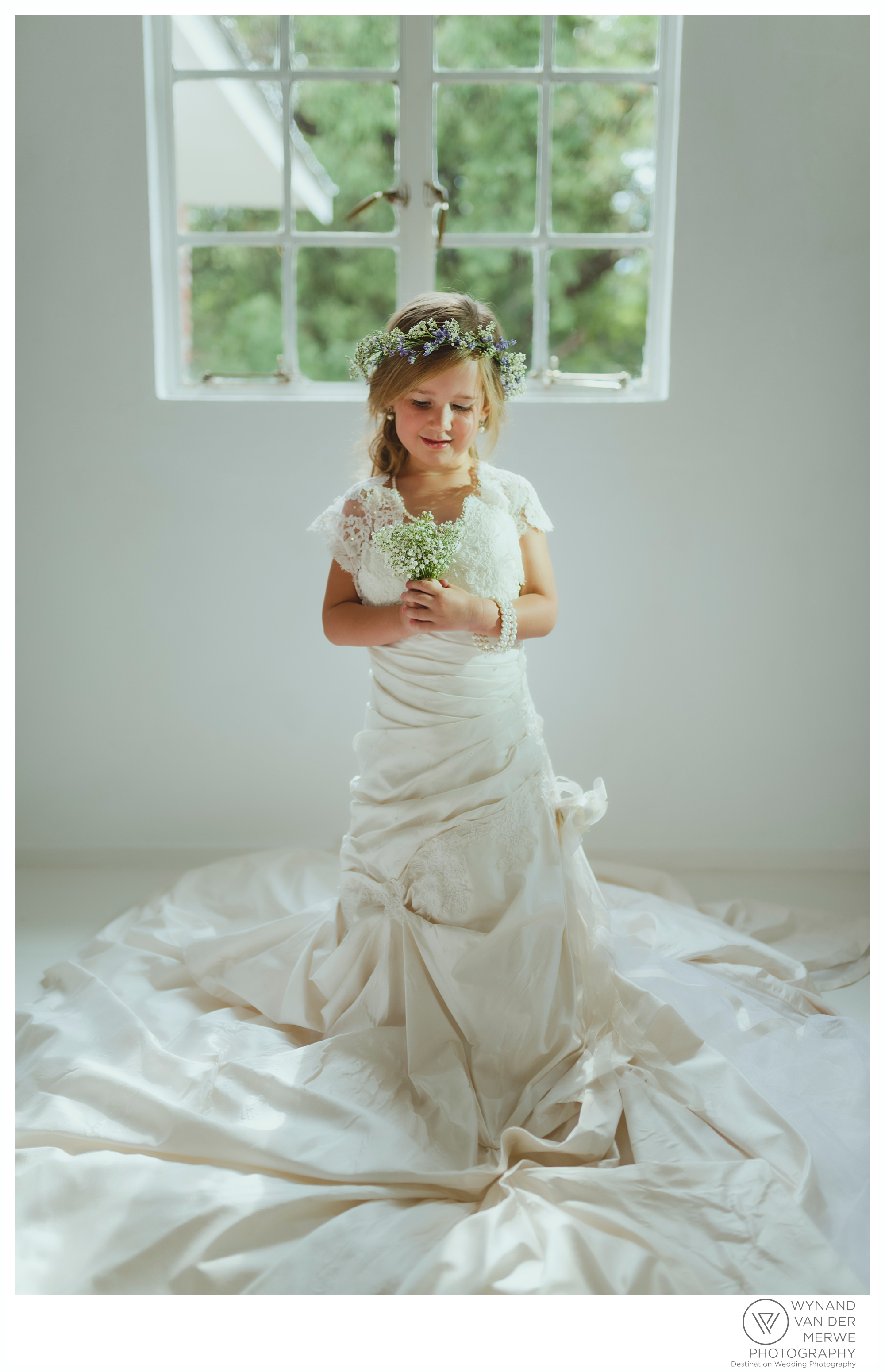 A little girl in her mom's wedding dress