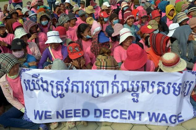 Cambodian garment workers sit behind a banner during a wage protest at the Freedom Park in Phnom Penh, on October 12, 2014 ©Tang Chhin Sothy (AFP)