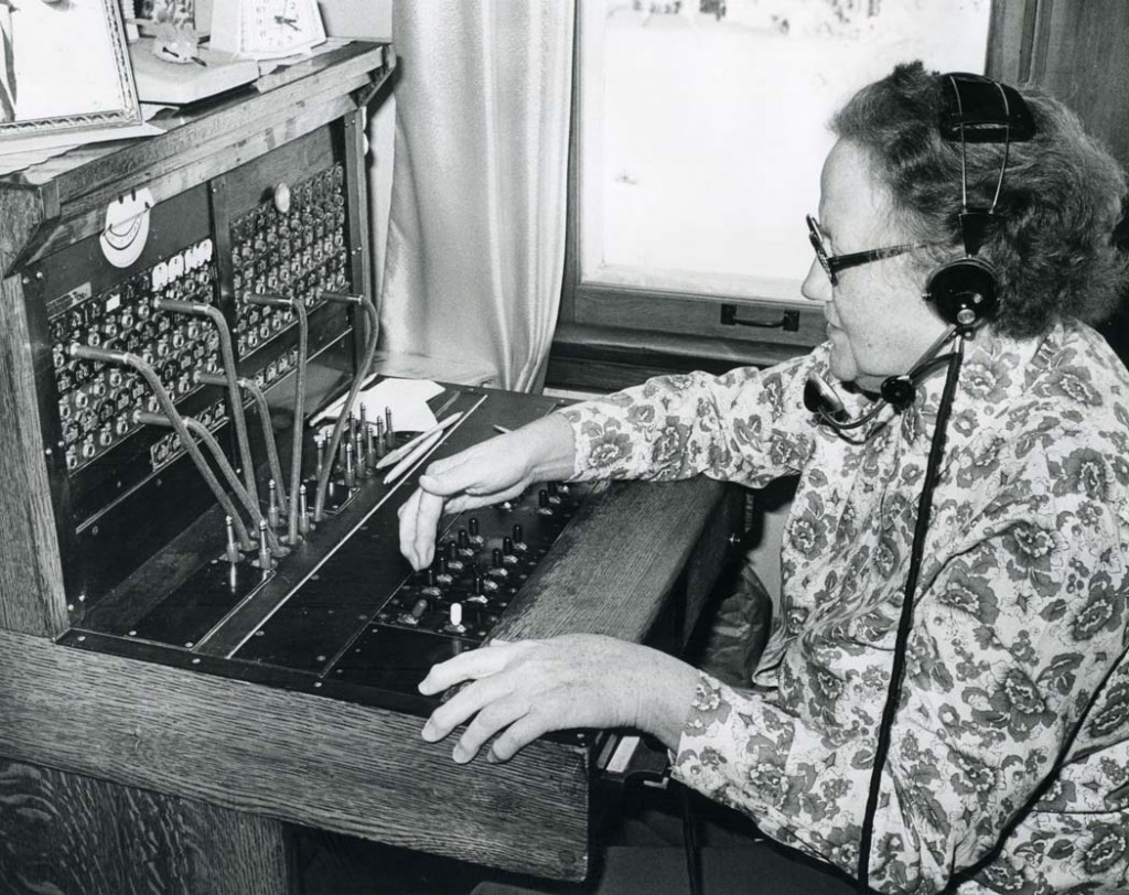 A woman operates an old-fashioned telephone switch board.