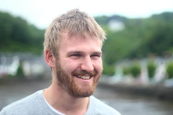 A young blond man with a beard smiles at something off camera.