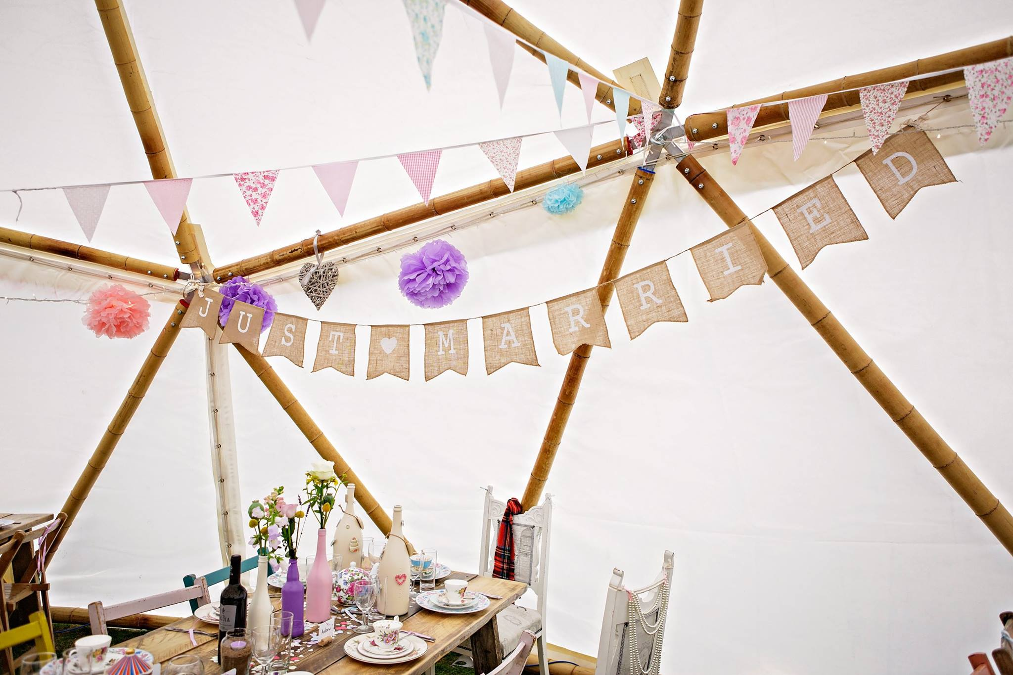 A willow chandelier lights up a geodome decorated with bunting and fairy lights.