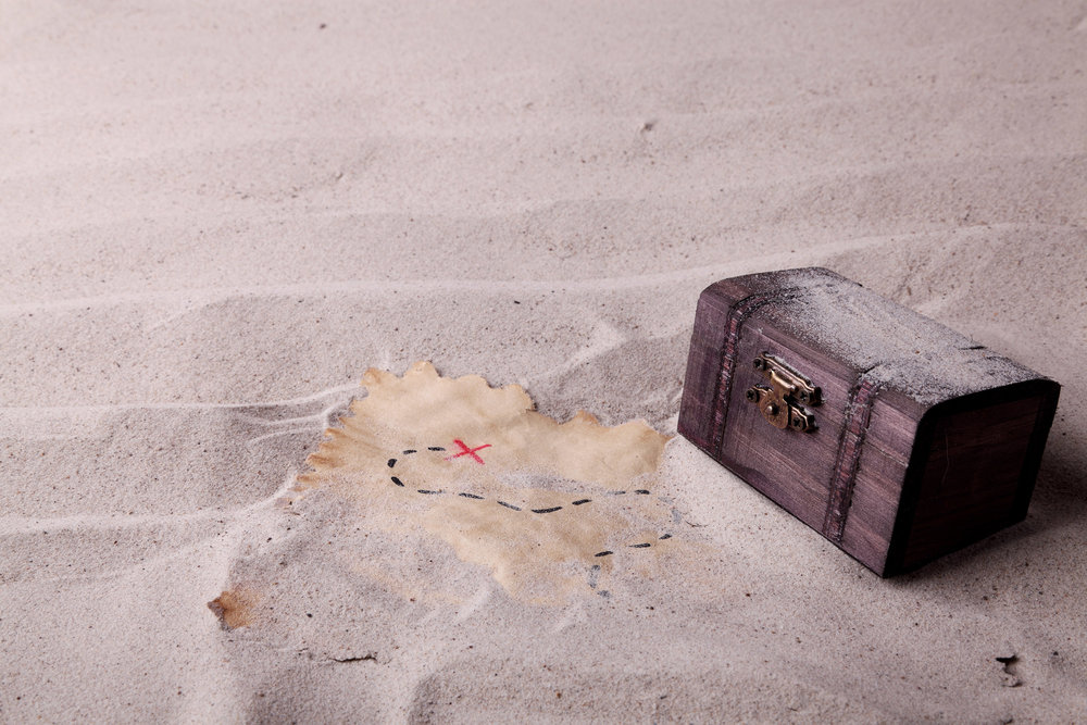 An old chest and a treasure map found in the sand