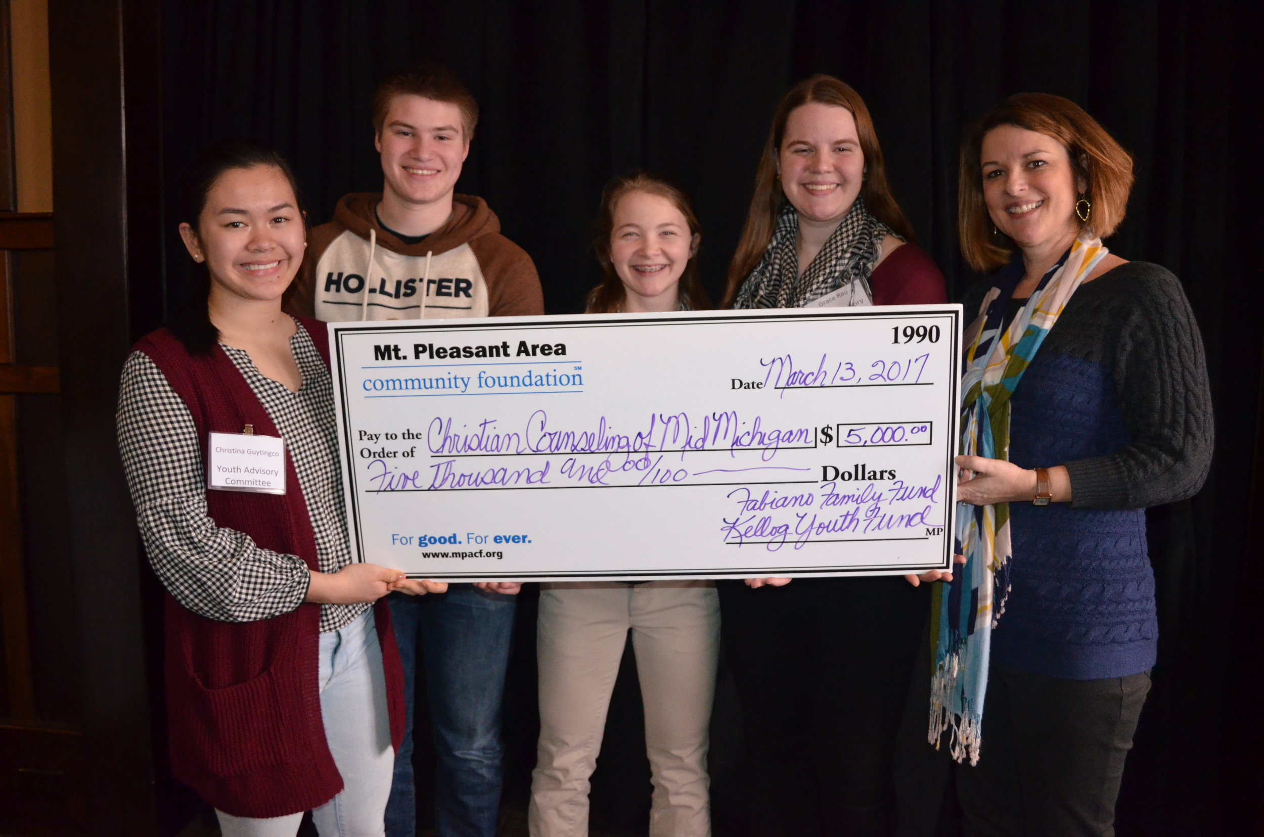 Members of the Youth Advisory Committee present a check to CCMM volunteer, Kim McBryde