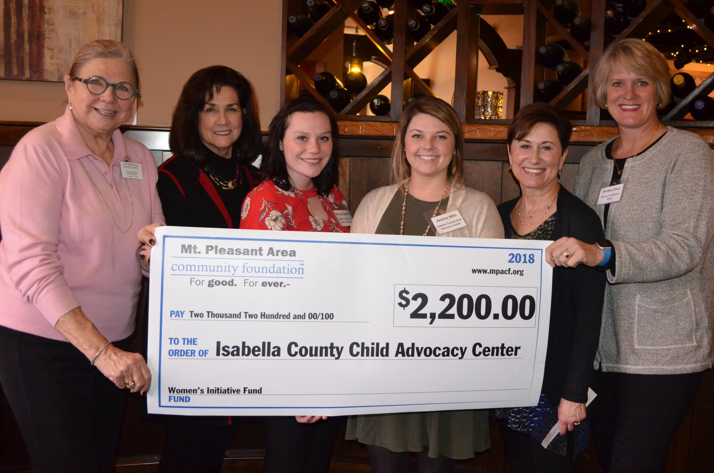 Members of the Women's Initiative Committee present a check to representatives of the Isabella County Child advocacy Center.