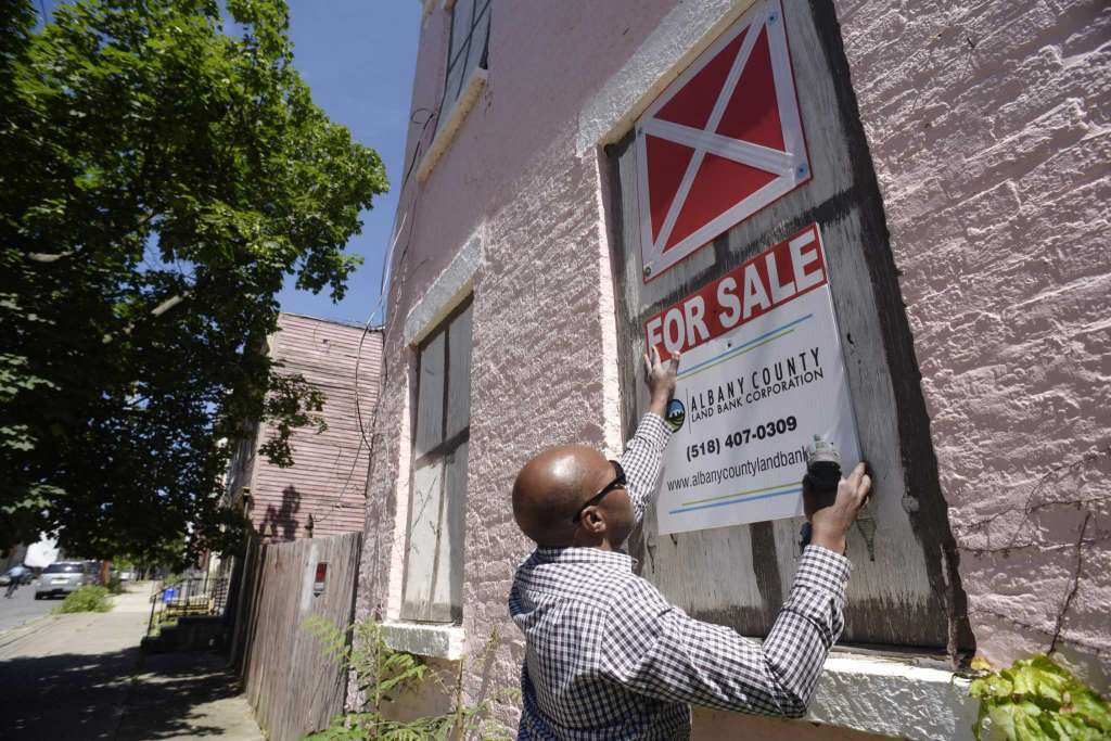 Irvin Ackerman, real estate sales associate for the Albany County Land Bank, hangs up signs on a building located at 29 Alexander Street on Wednesday, June 14, 2017, in Albany, N.Y. The Albany County Land Bank recently took over ownership of the property. (Paul Buckowski / Times Union)