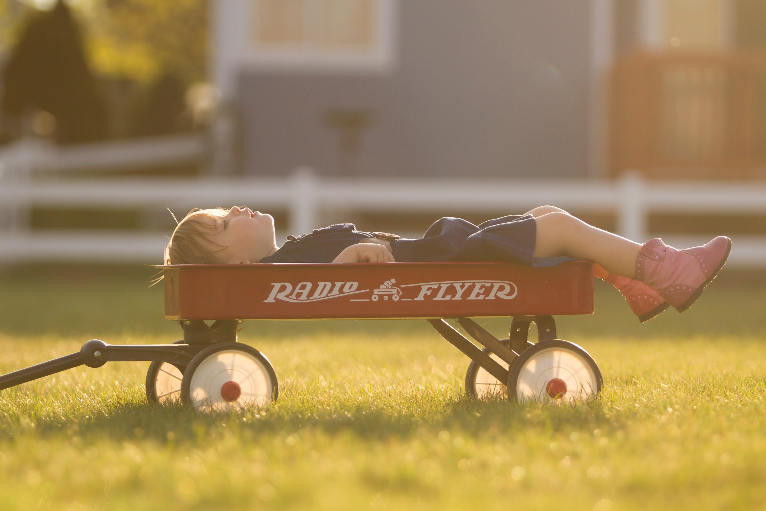 Little boy napping in a Radio Flyer wagon.