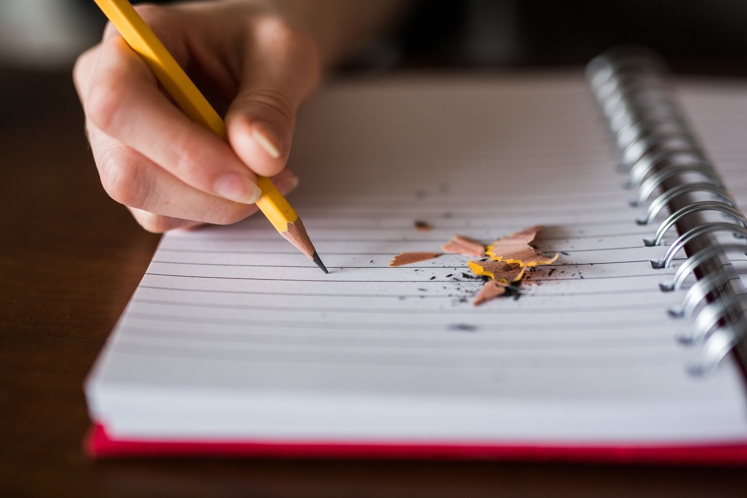 Image of a woman writing with a pencil in a notebook
