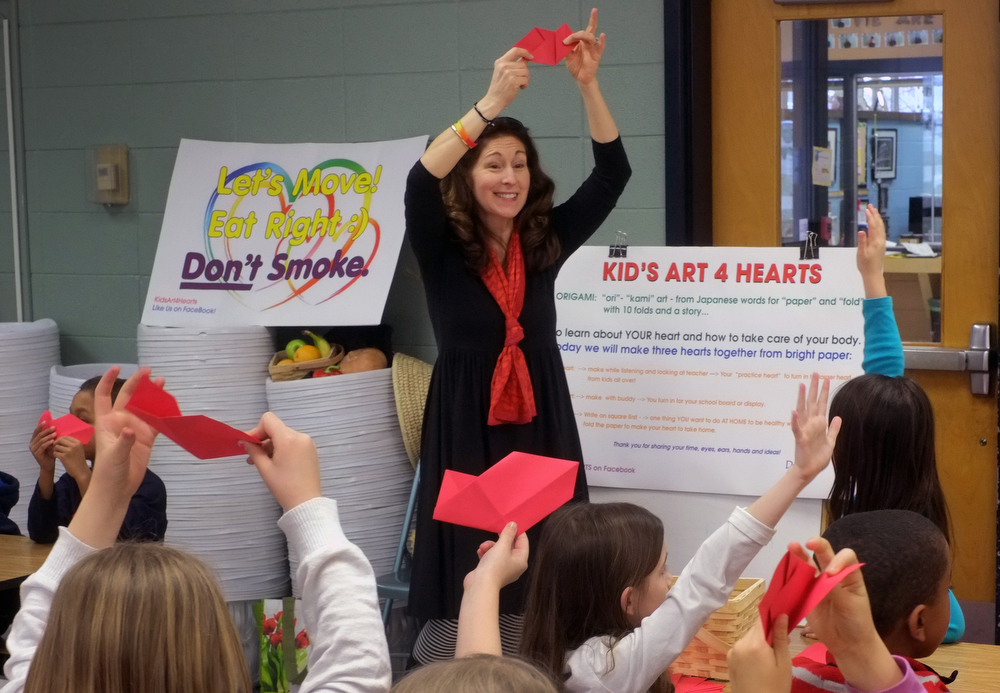 Dr Cerel-Suhl teaching the first folds of the first of three origami heart; the second and third hearts are done by teams in a 21st Century Curriculum. January 2016. photo  Lexington Herald-Leader, Tom Eblen