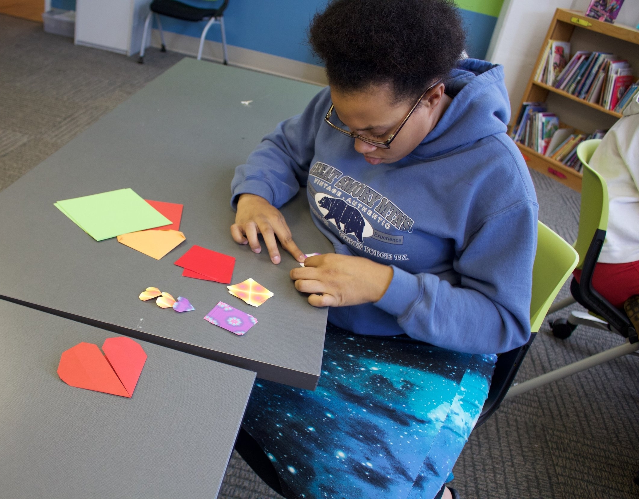 Family Care Center student making individual hearts for group project after KidsArt4Hearts lesson.
