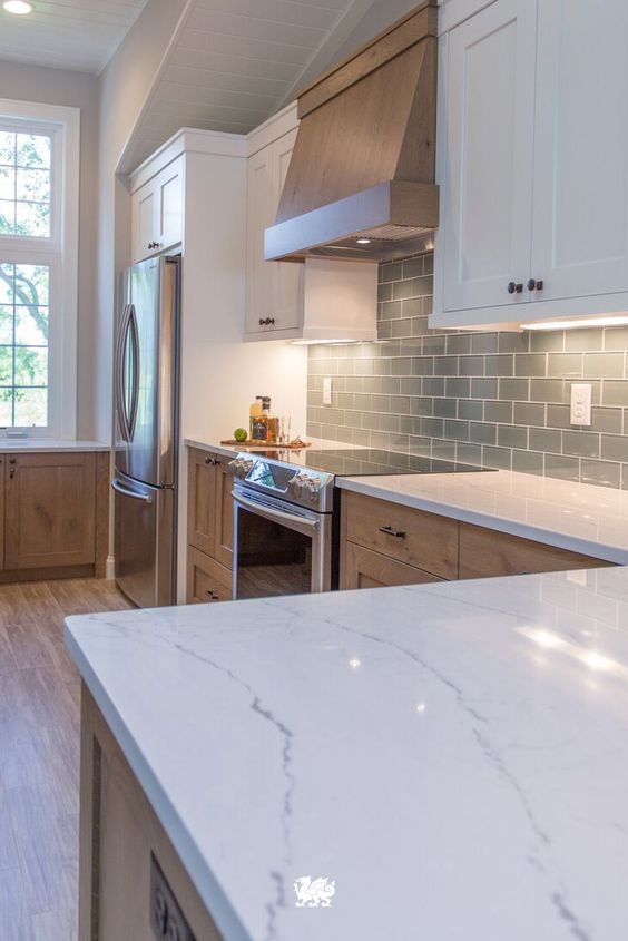 Perfect Pairing - This is a perfect pairing of texture and a neutral palette. The gray backsplash compliments the upper cabinets and countertops while breaking up the white and pairs nicely with the clear lacquered base cabinets and feature hood range.