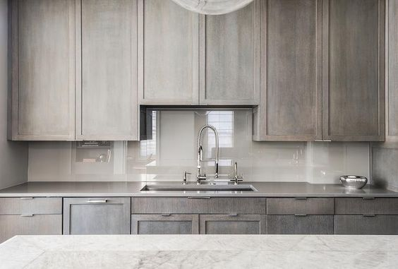 Apartment with Style - Even apartments and condos can have mega style! Pair gray stained cabinetry with a high gloss backsplash to keep a small kitchen feeling spacious!