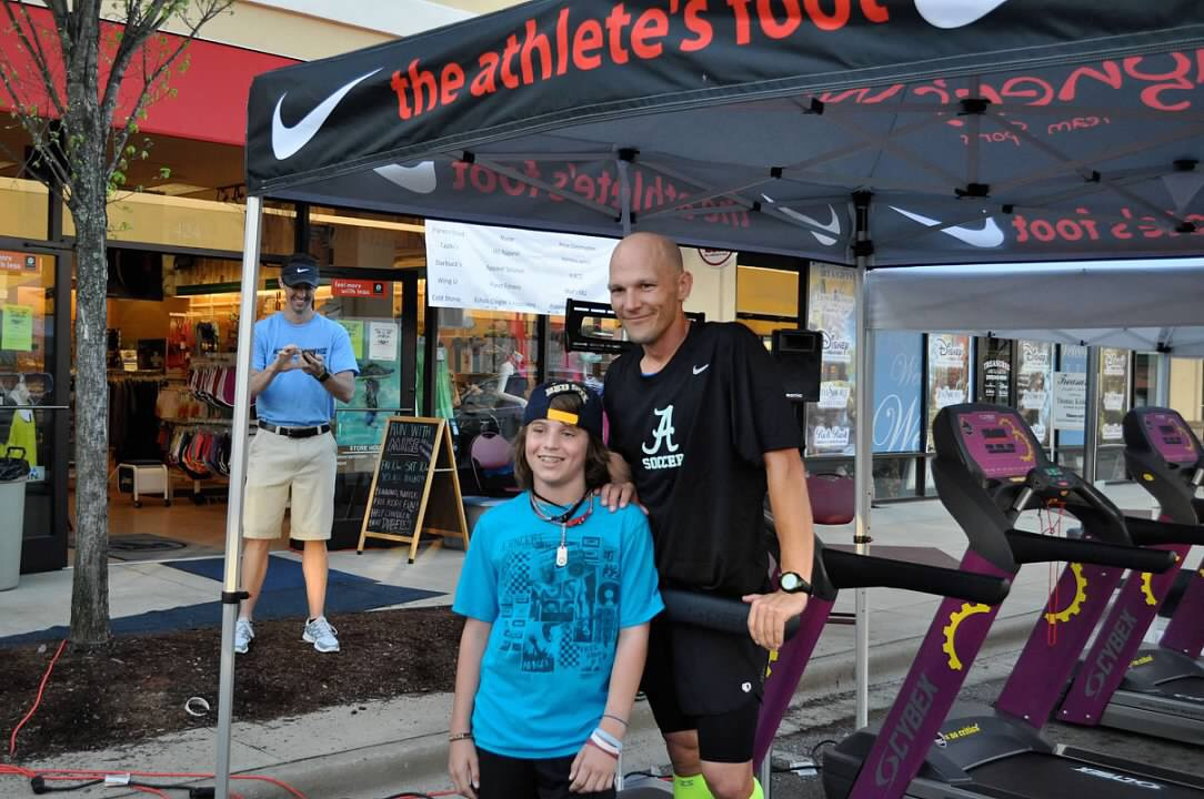 Cole and Mike Bissell stand together during the 100-mile treadmill fundraiser.