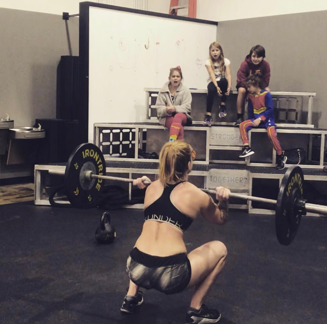 Arsenault's children cheer her on as she workout at Irontribe in Tuscaloosa.