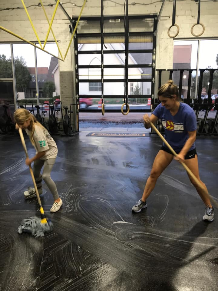 Arsenault and her daughter, Avery, mop the Iron Tribe Fitness floor together.