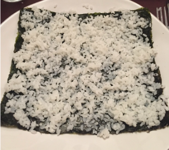 Next you take out a seaweed wrap and put it on your plate. Be gentle as these wraps are fairly delicate and will rip! Spread (carefully!) sushi rice onto the wrap. You want the whole thing to be basically covered up, especially the corners as this is how the wraps gets held together.