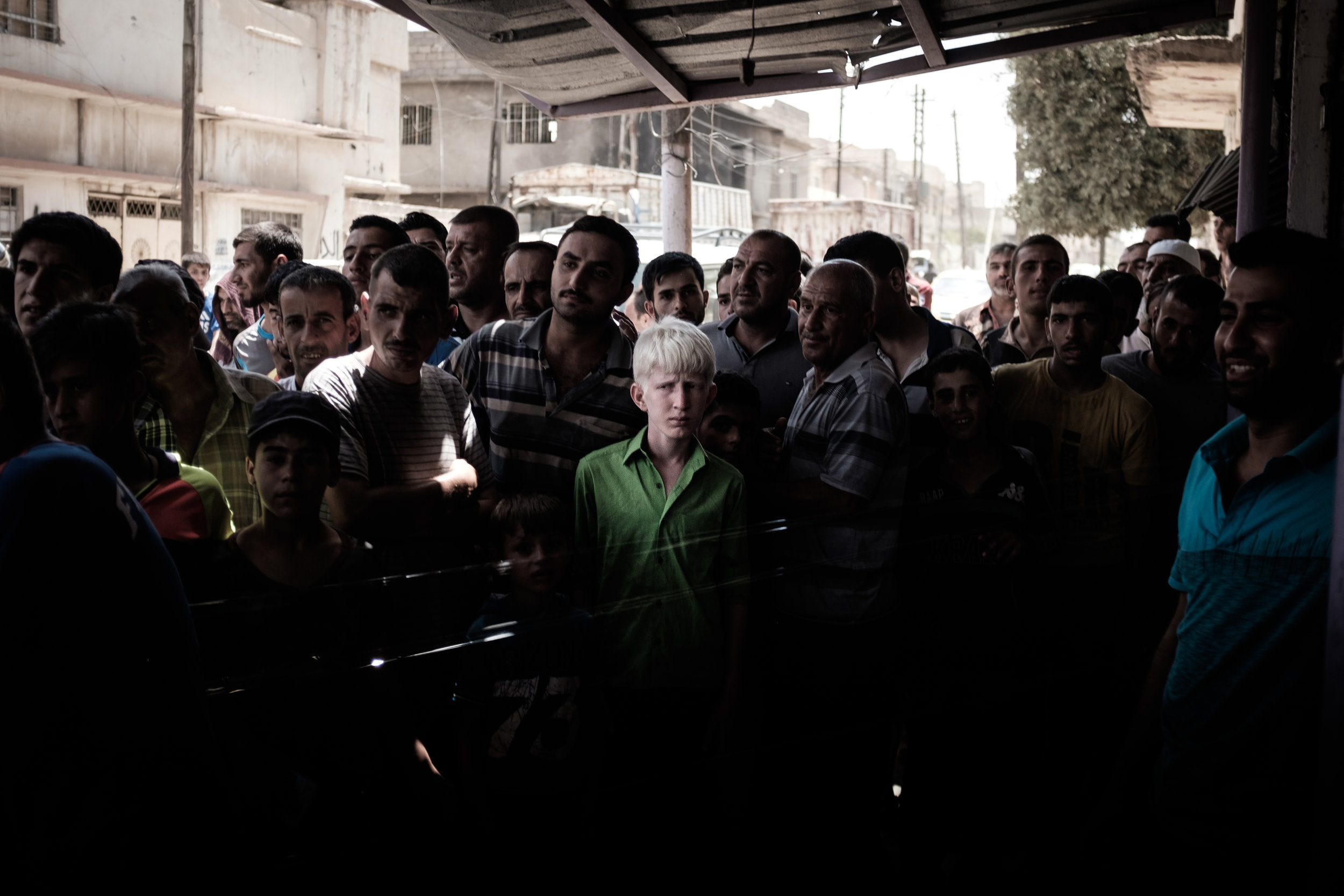 A boy with albinism stands in a crowd of people from his neighbourhood in West Mosul awaiting aid distribution from a local NGO. Since the fighting pushed through the area and into the Old City, this was the first humanitarian aid convoy to arrive in the area in a number of weeks.