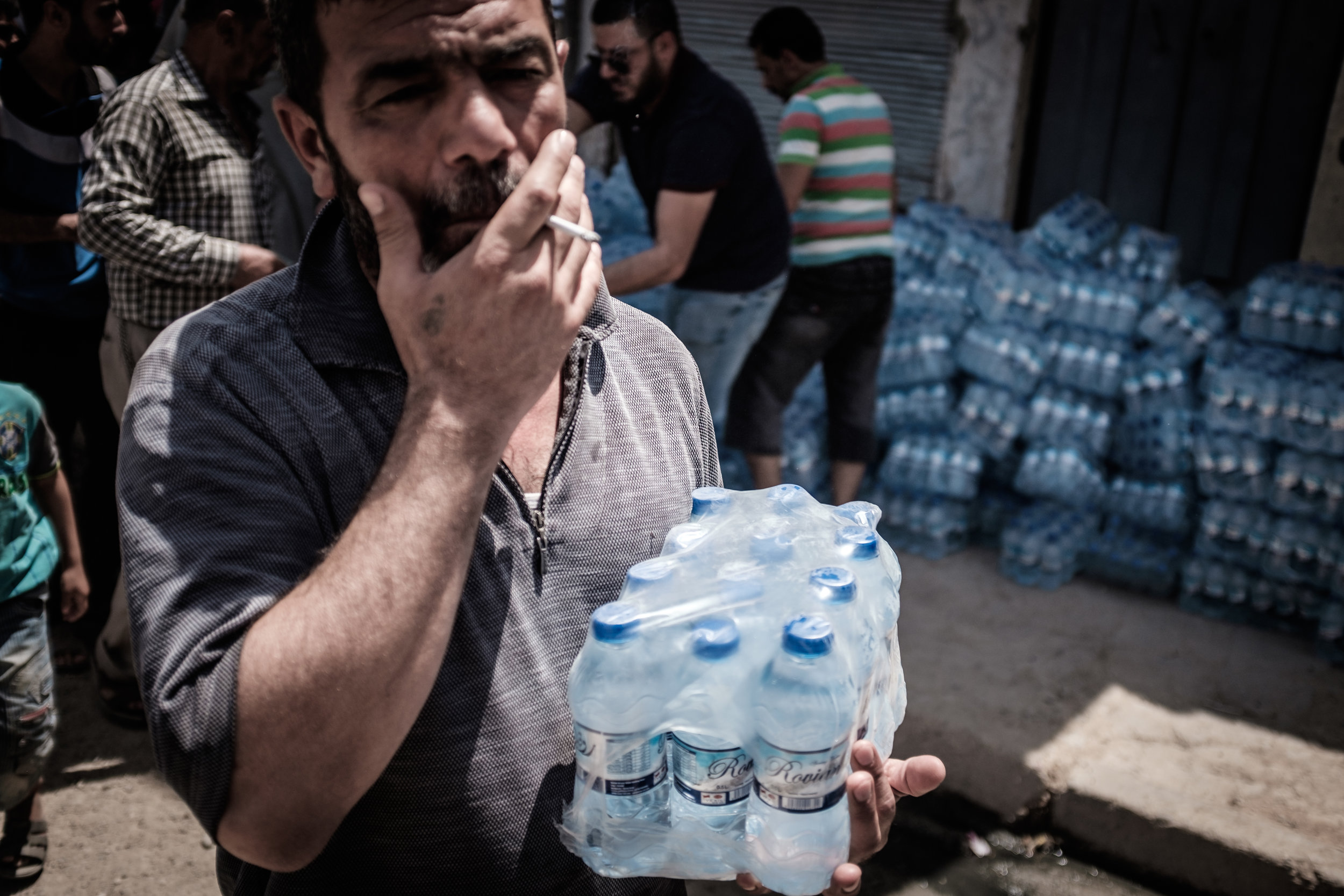 A man carries bottles of water that have been distributed by a local NGO as part of the first distribution of it's kind to this area in a number of weeks
