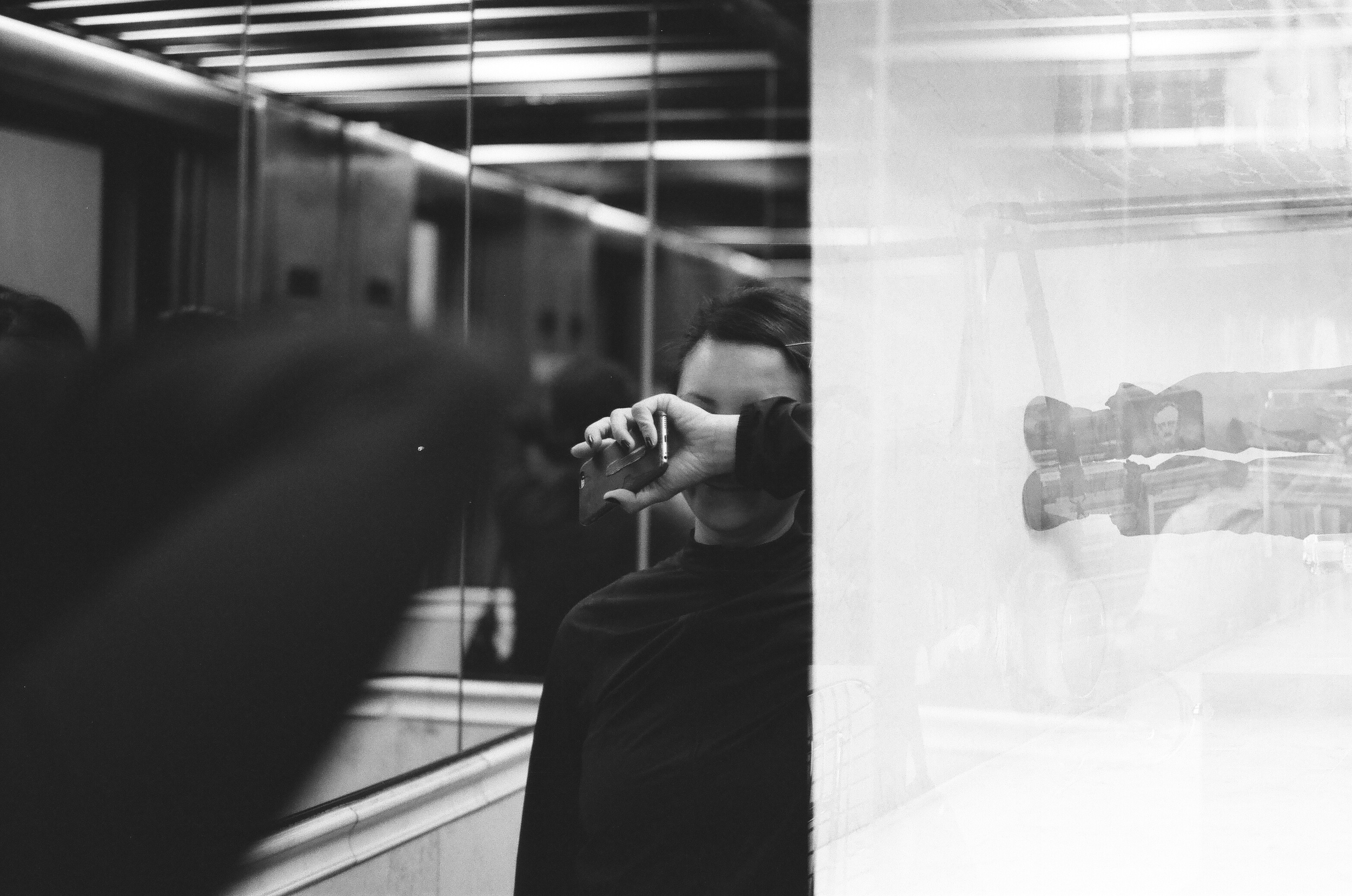 The bottom of the multiple exposure portrait overlapping with my wife being sleepy in an elevator. Leica M-A, Summicron 50mm 2.0, Ilford Delta ISO400 35mm film, improperly cut by the lab? My fault again? I wouldn't rule that out either.