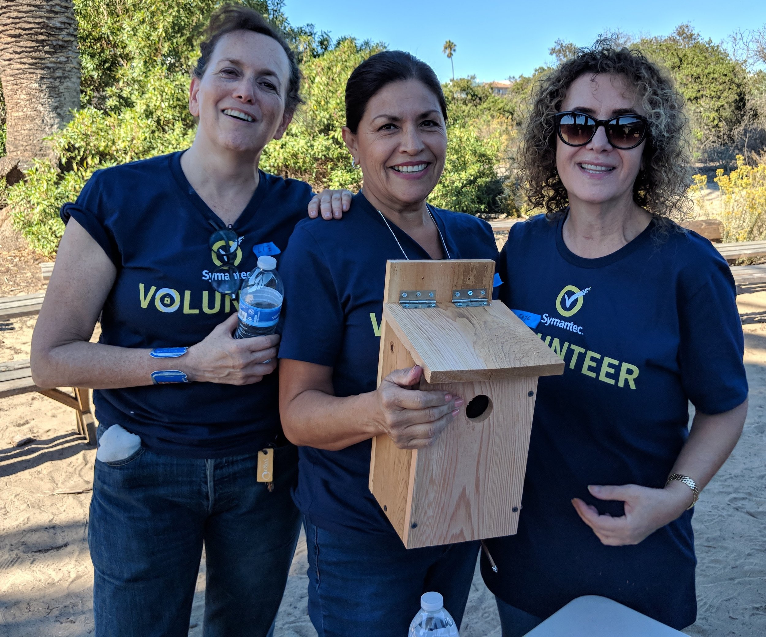 Symantec employees hold nesting boxes they created as part of a creek cleanup they participated in near Los Angeles in 2018.