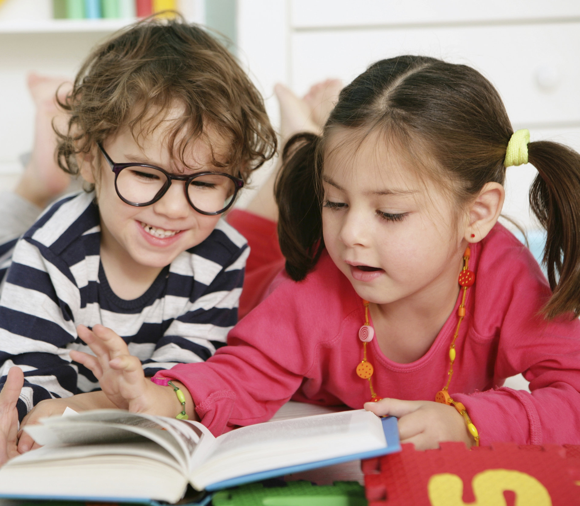 "Toddler boy and girl reading. Links to ""Where We Are"" page."