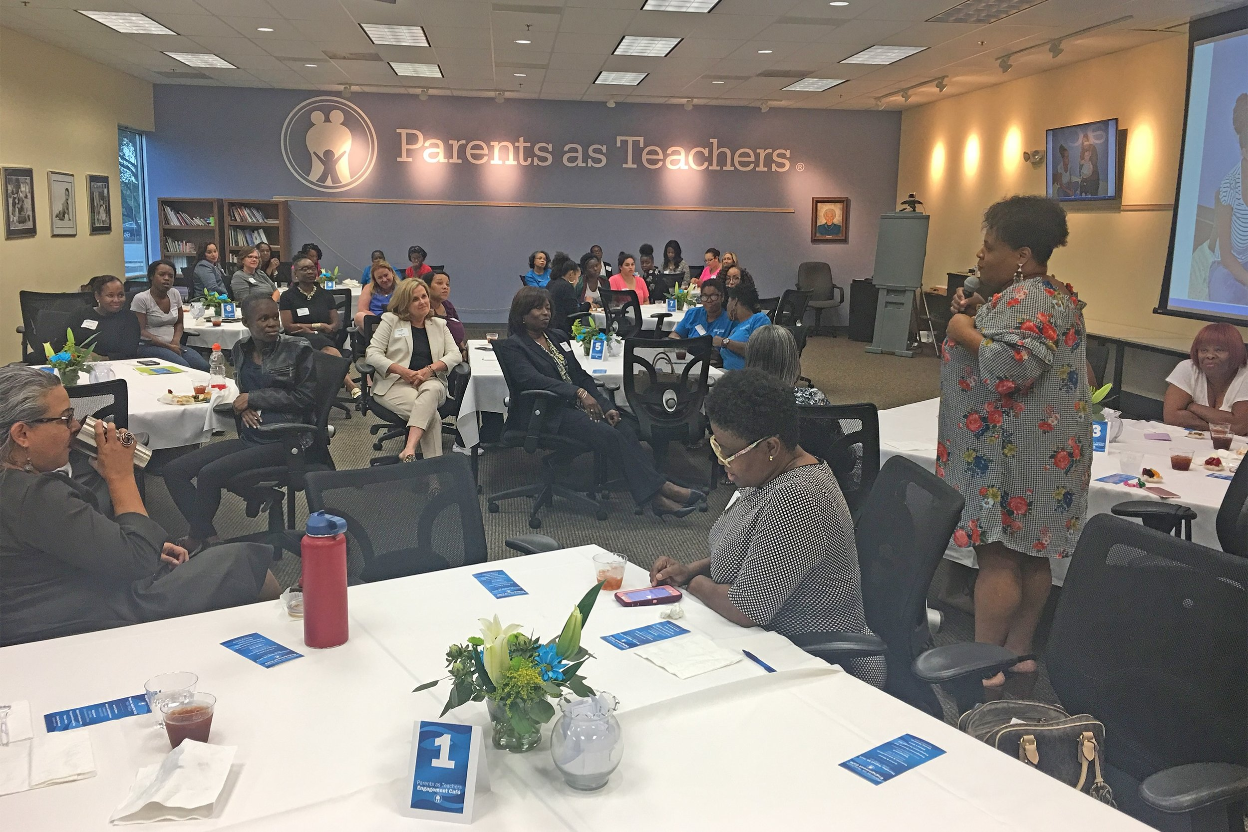 Ellicia Lanier, (standing) an associate professor at St. Louis Community College at Florissant Valley, addresses Parents as Teachers inaugural meeting of the Professional Women's Engagement Café as part of PAT's Women's Partnership Network.