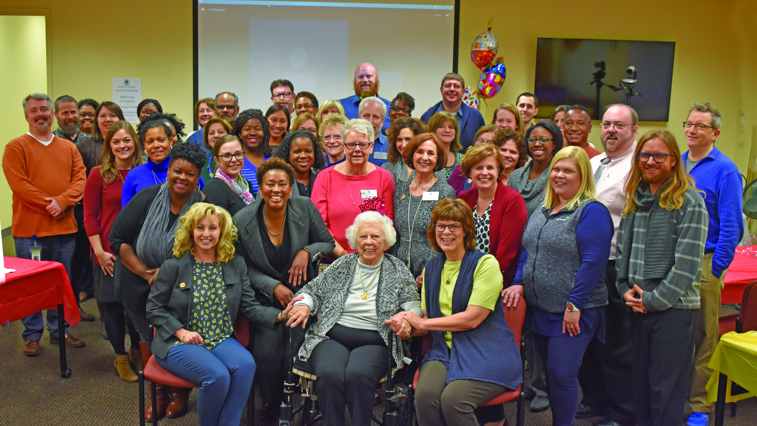 Parent educators and staff at the Parents as Teachers National Center in St. Louis, MO pose with Parents as Teachers Founder Mildred Winter (seated center) and Constance Gully, the organization's president and CEO, (left) during Winter's 98th birthday celebration. The day was also recognized as National Parents as Teachers Day and the kick-off to Parents as Teachers 35th-anniversary activities.