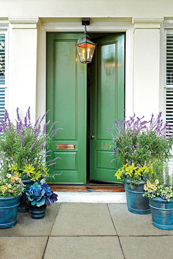 Love the curb appeal of this inviting entry.The high gloss front door in the gorgeous kelly green mixed with the jewel tone planters really draws you in. I don't know about you but my interest is certainly peeked to see the inside of this home!  Techniques like this are a great way to create curb appeal to a home when you have it on the market. There is something about doing something a bit more outside the box that makes people want to delve further. For me these are the spaces I like the best.