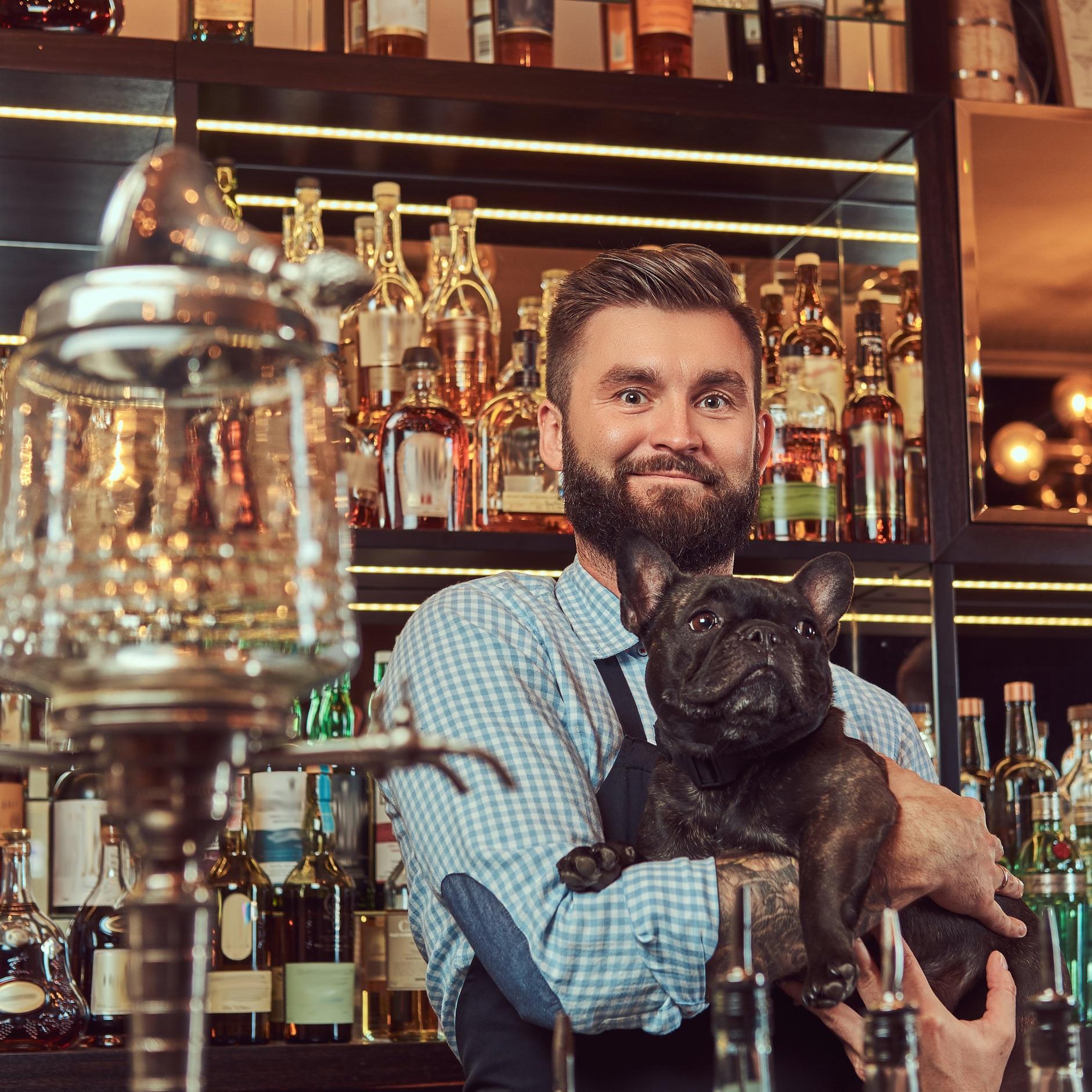 Canva+-+Bartender+Carrying+a+Black+Pug+in+Pub.jpg