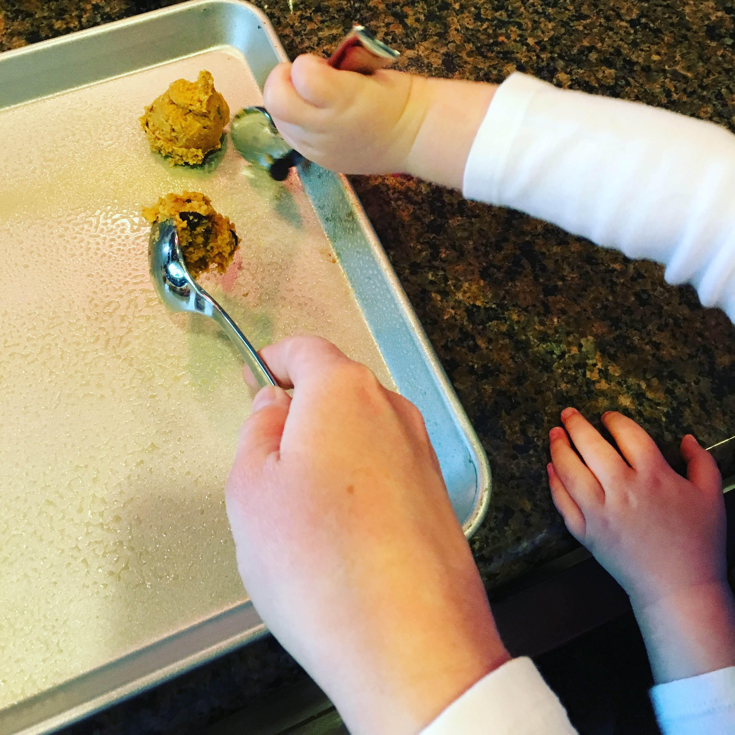Hold the dough on one spoon, and let your kiddo spoon it onto the baking sheet.