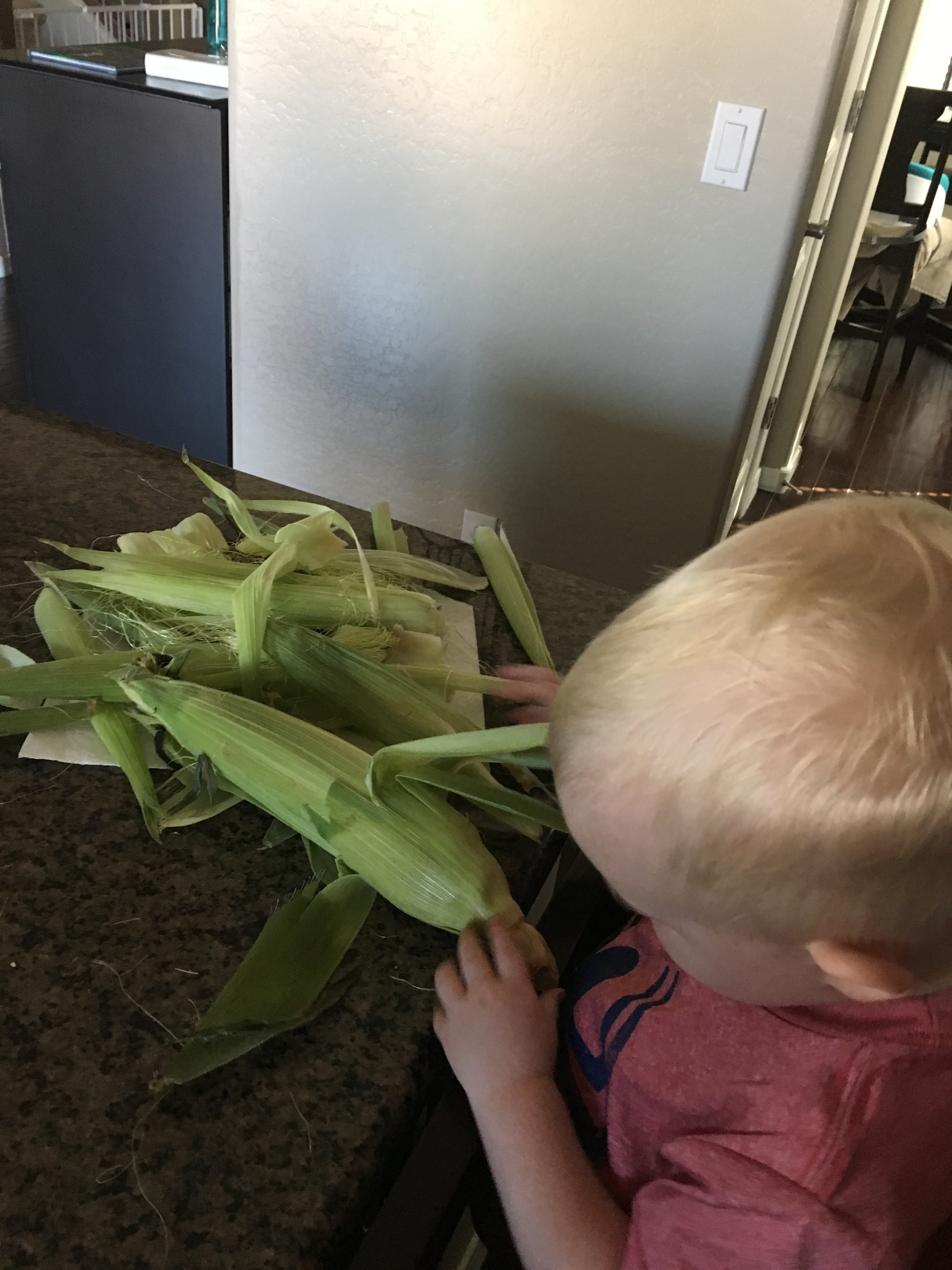 """Helping"" with corn ... until they're old enough to help with corn."