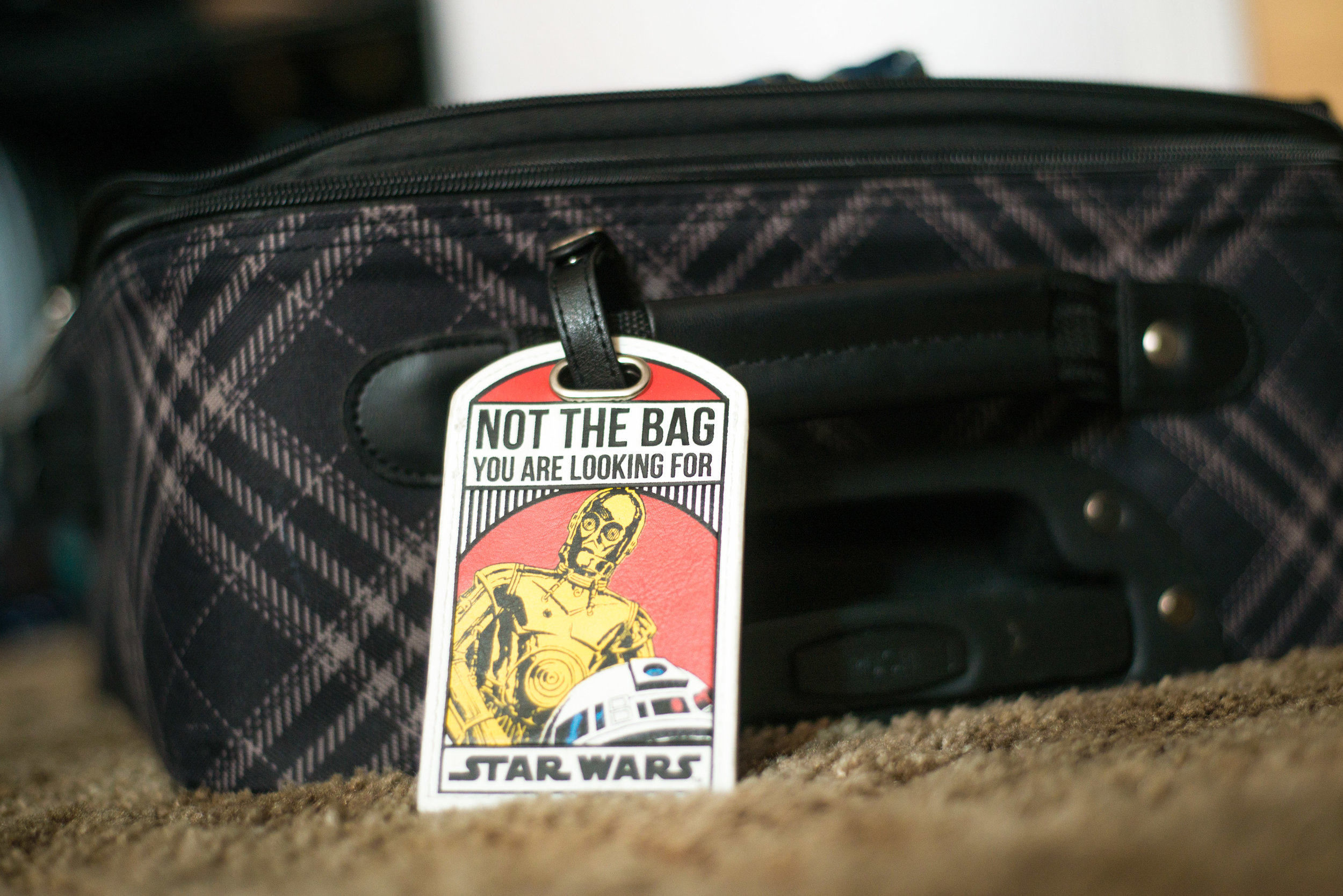 """How to pack for a two week vacation - in a carry on. Luggage tag reads """"Not the bag you are looking for with C3PO and R2D2 from Star Wars."""