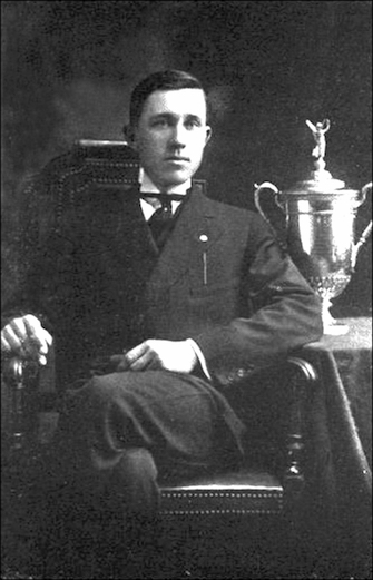 Johnny McDermott, the first native-born U.S. Open champion, sits with his trophy from 1912.