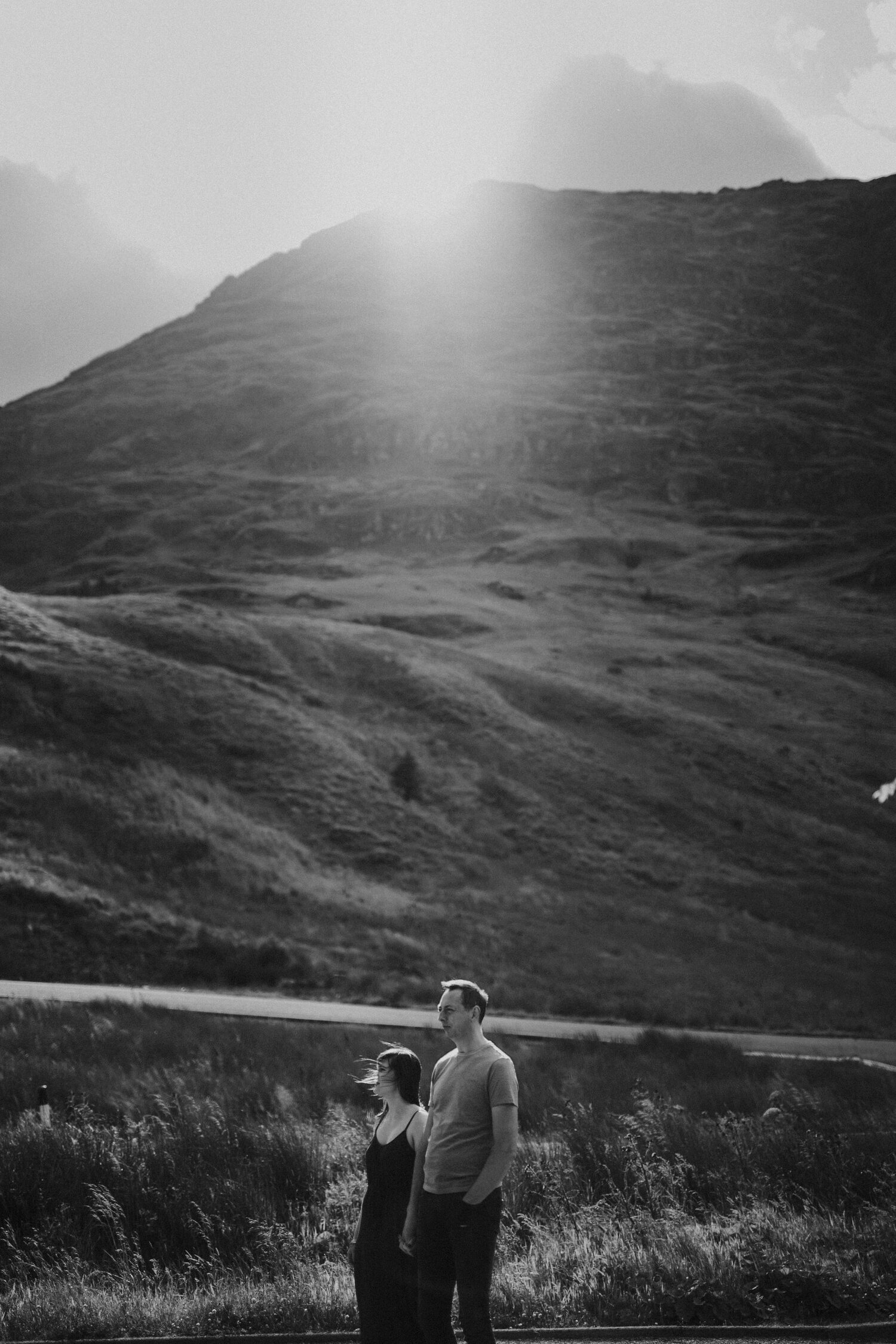 a couple standing in teh mountains during sunset black and white picture