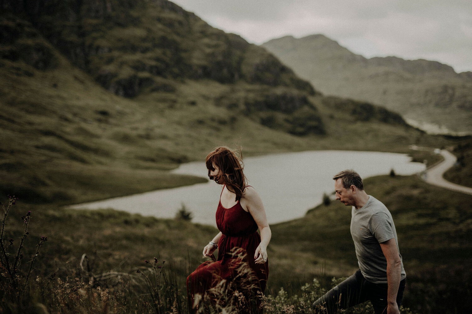 woman in dark red dress walking up the hill in mountains man follows her