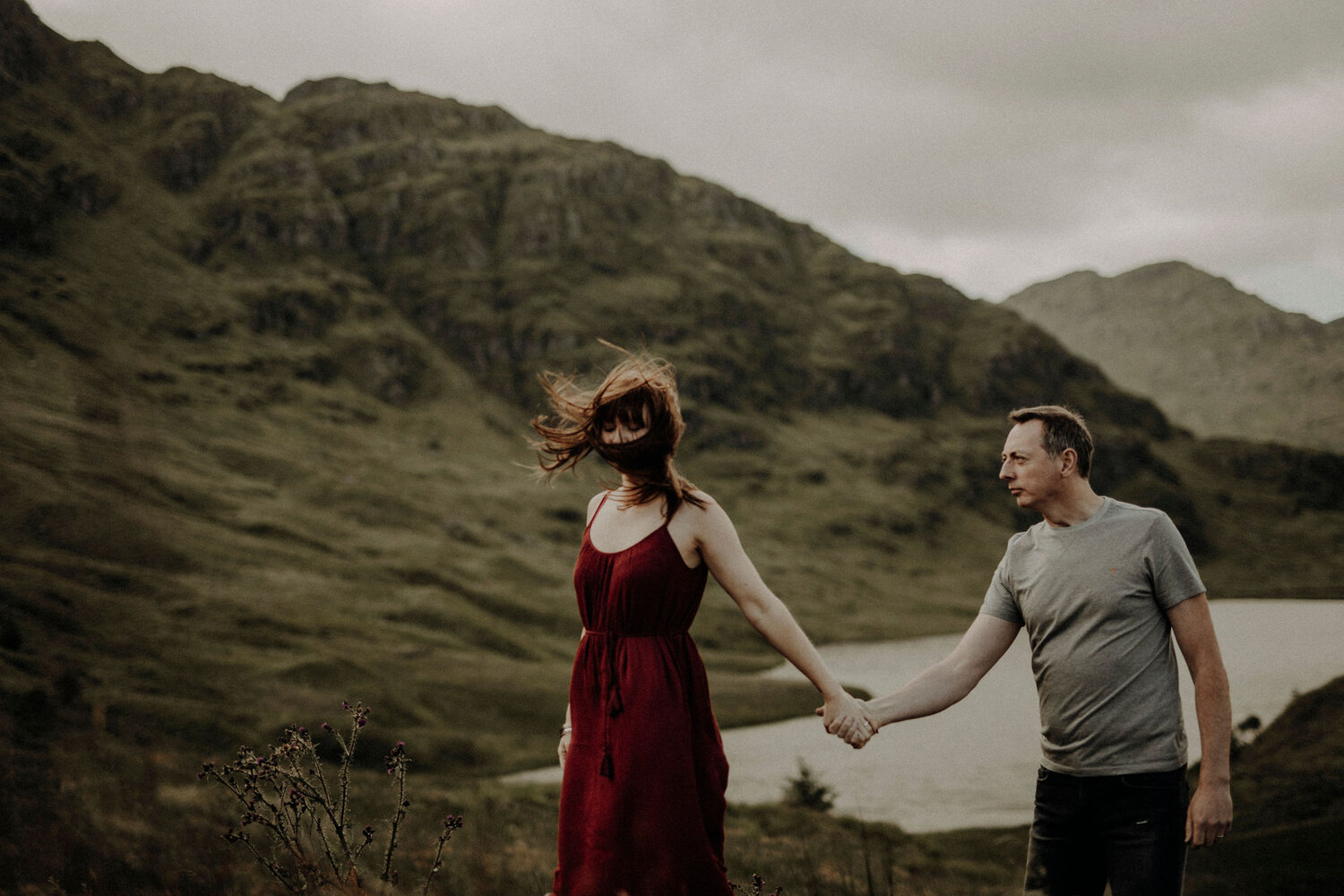 woman and man holding their hands wind blowing hair in mountains with a lake behind