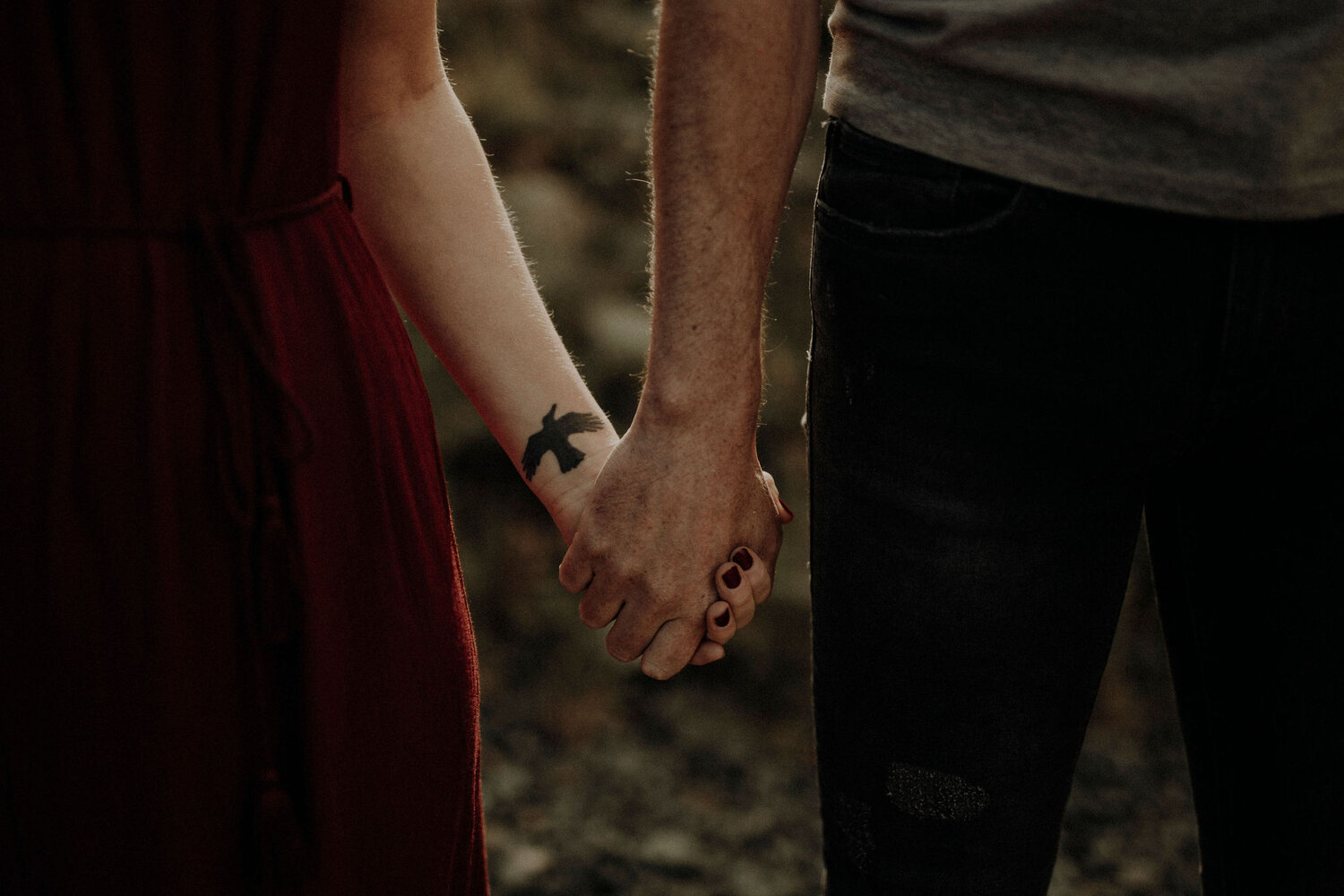 woman and man holding their hands bird tattoo on her wrist