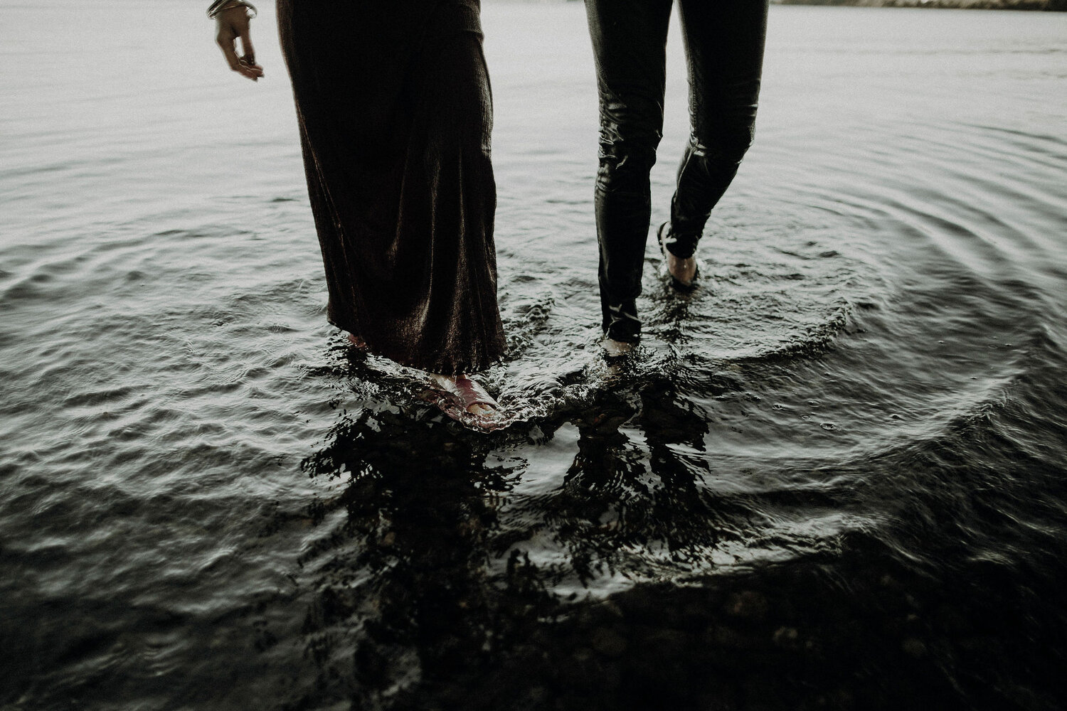 a couple walking out the water in clothes
