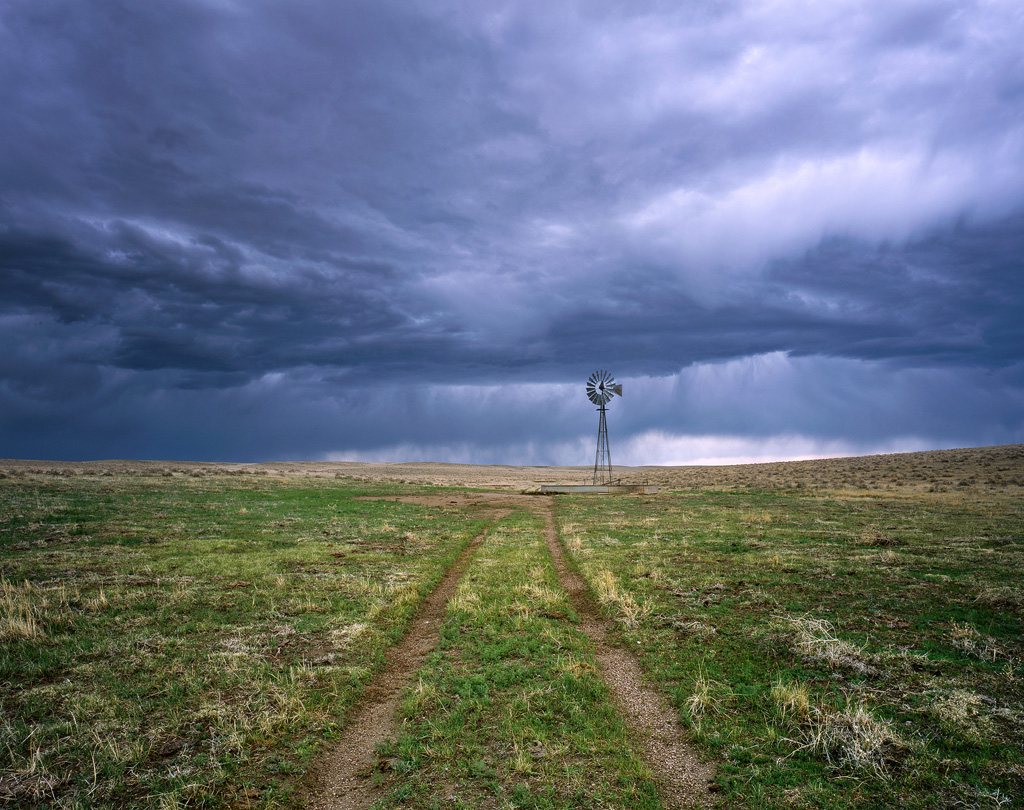 """""""Windmill, Two Track, Storm"""" – I biked about 50 miles from home to spend the night on the Pawnee Grasslands, a bit of a May tradition for me. Late in the afternoon the skies turned threatening and I had to seek shelter, but not before capturing this image during the calm before the storm. Prints available."""