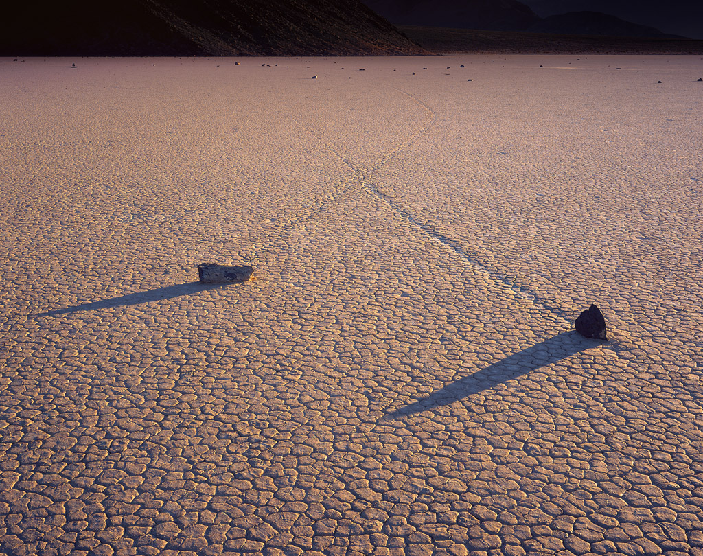"""X Trails"" - Sailing stones leave a distinct letter in the dried earth. Late afternoon light stretches the shadows and obscures reality in this otherworldly environment."