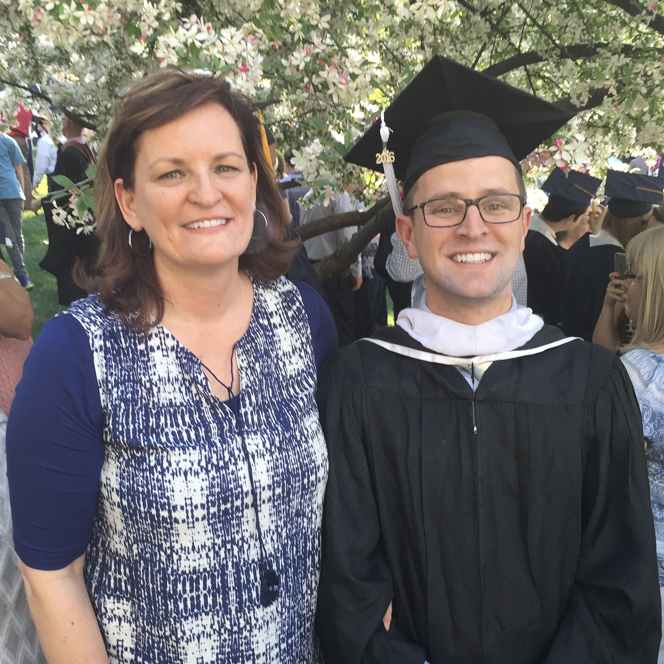 Ellen King standing next to Daniel King in his graduation cap and gown.