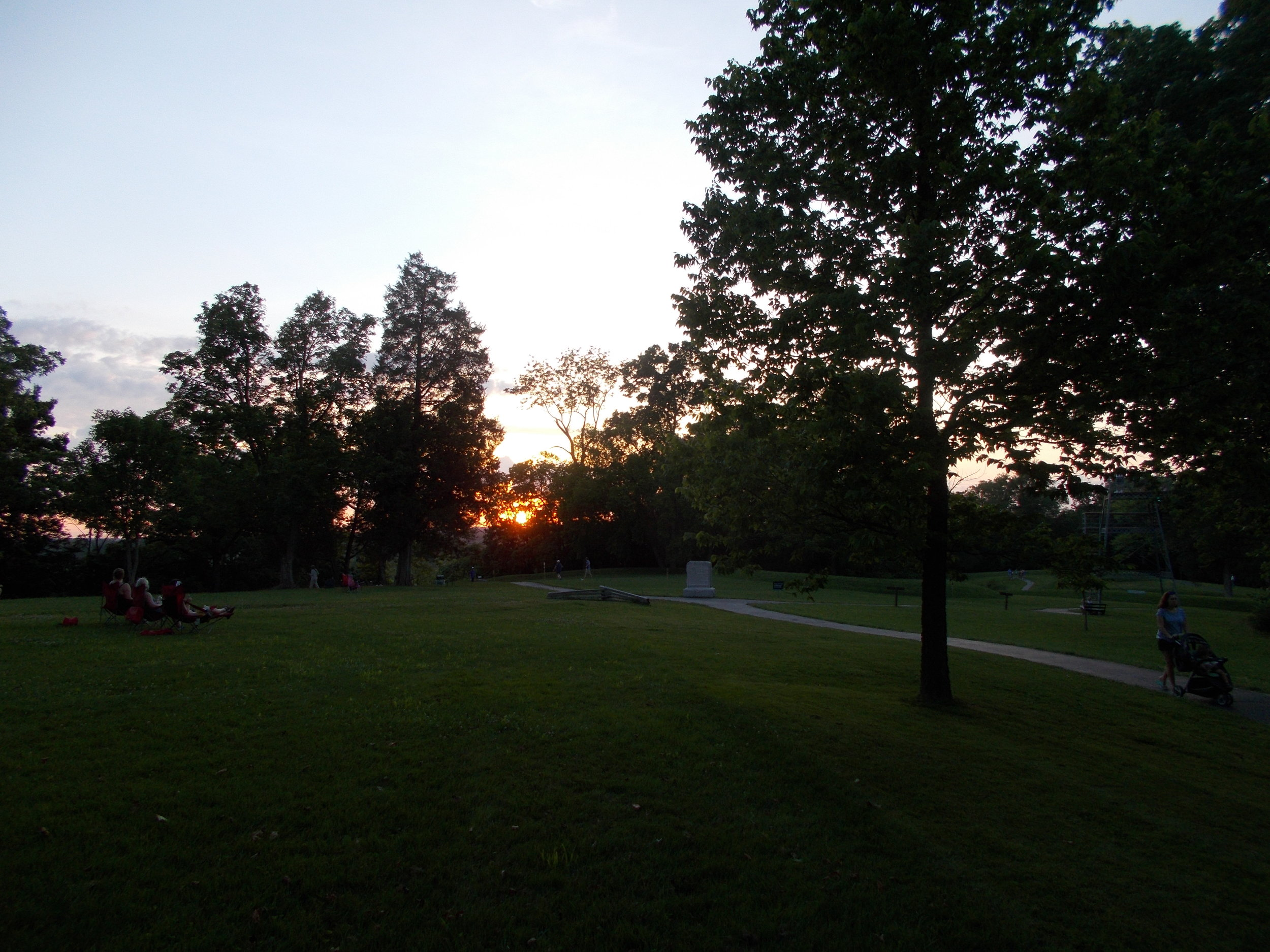 image: sunset at Great Serpent Mound, 06/17/2017; photo looking towards coiled tail and setting sun beyond -- body of Serpent stretches towards right of photo and curves back towards setting sun.