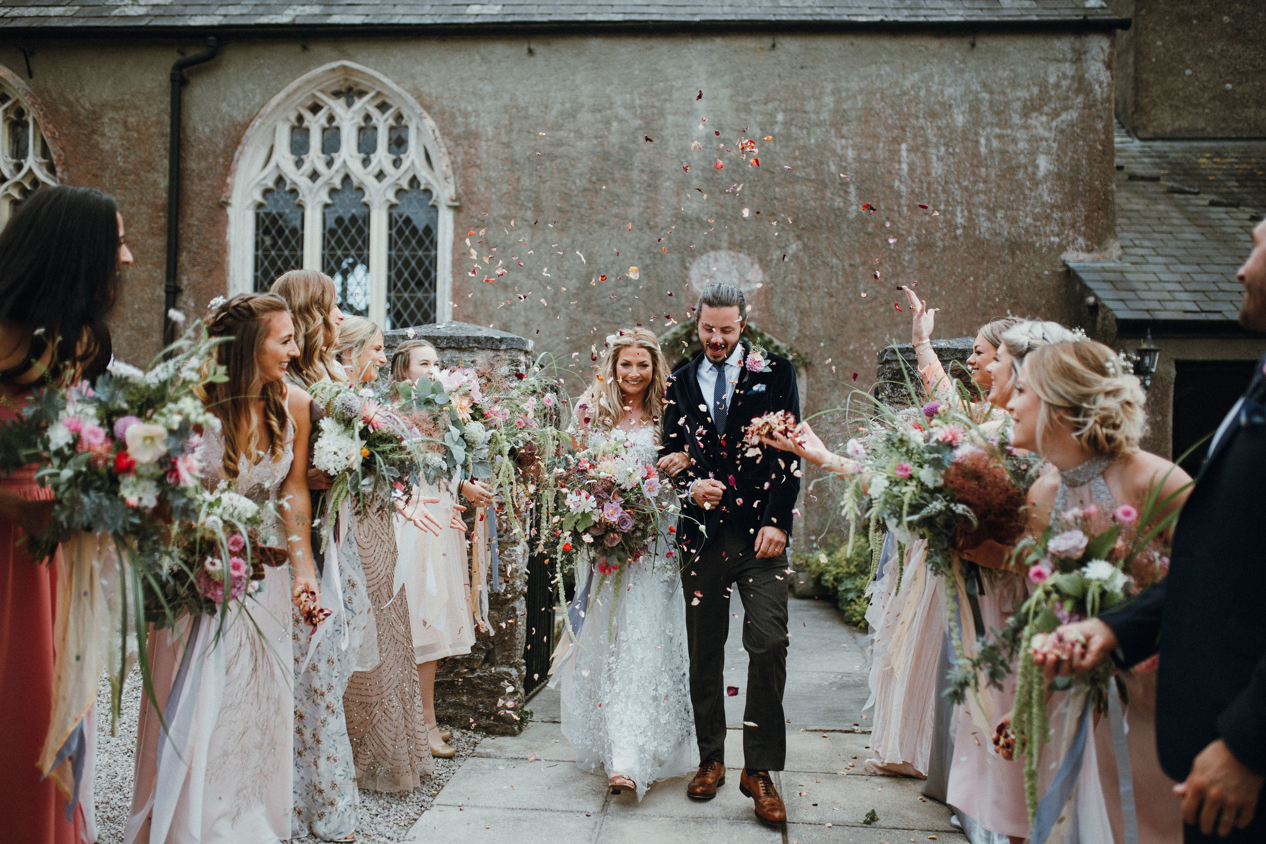 Wedding couple walking through confetti